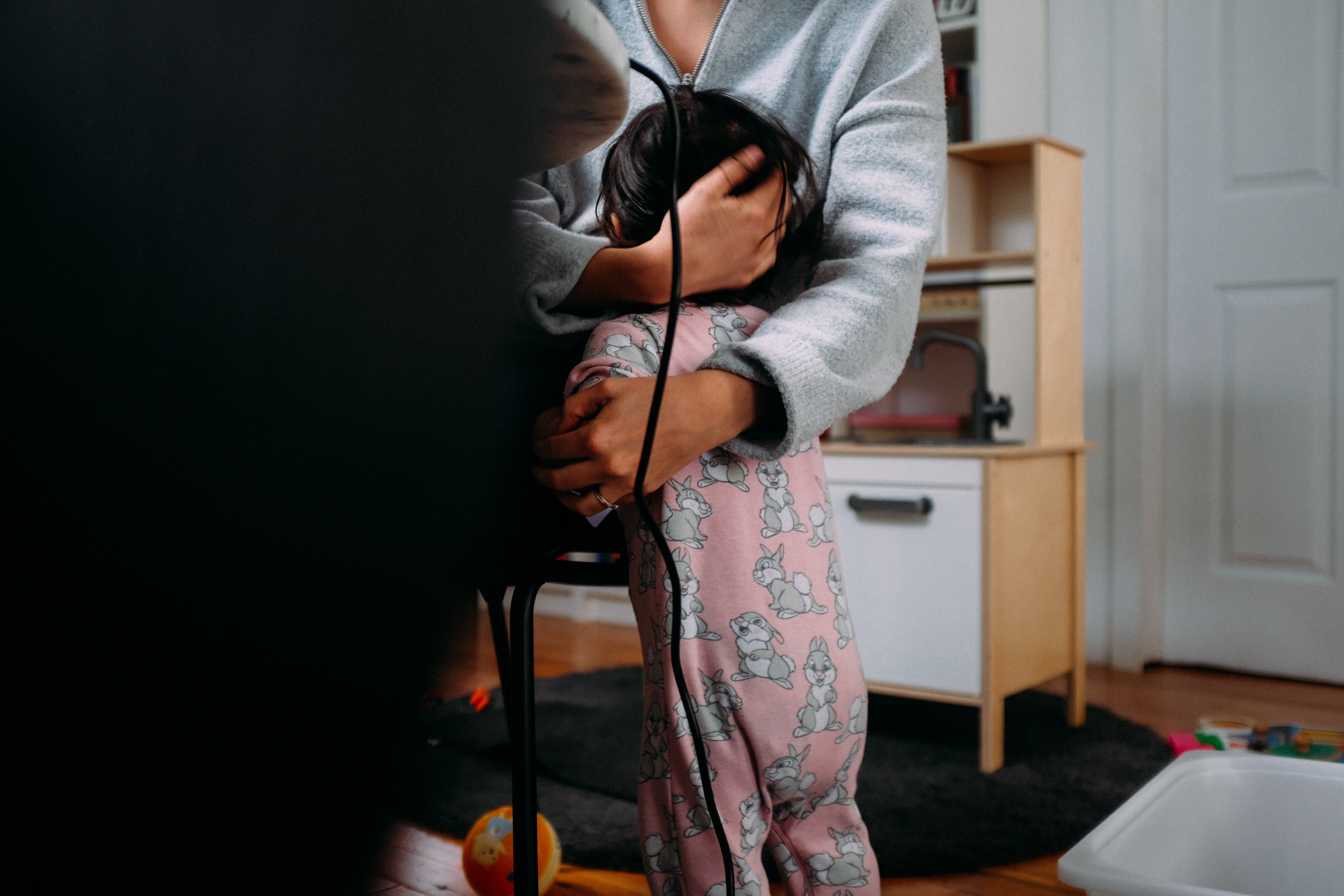 A parent cradles the head of a toddler wearing pink footie pajamas.