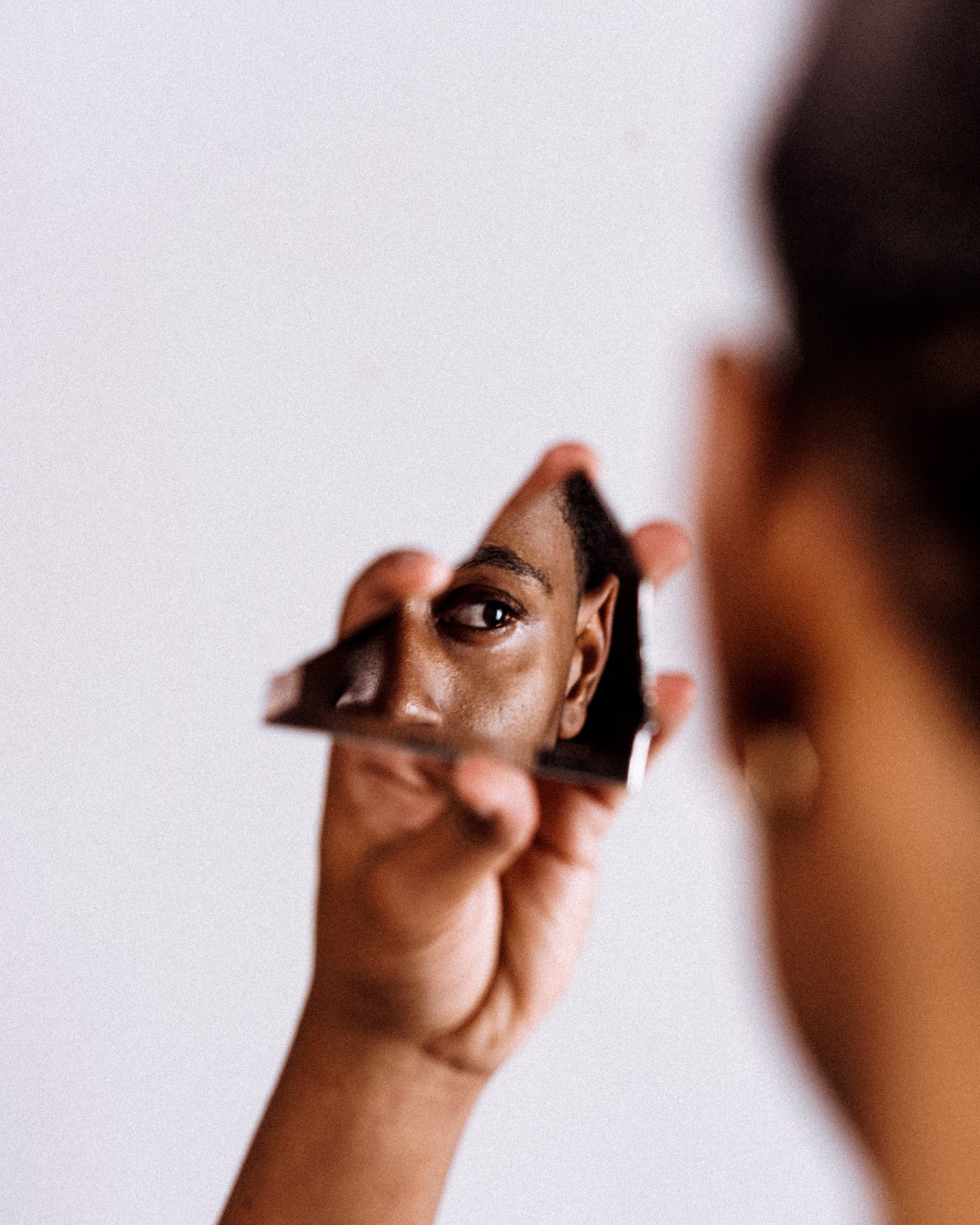 A black person holds a jagged piece of mirror, looking into it, as the camera captures the reflection oftheir eye.