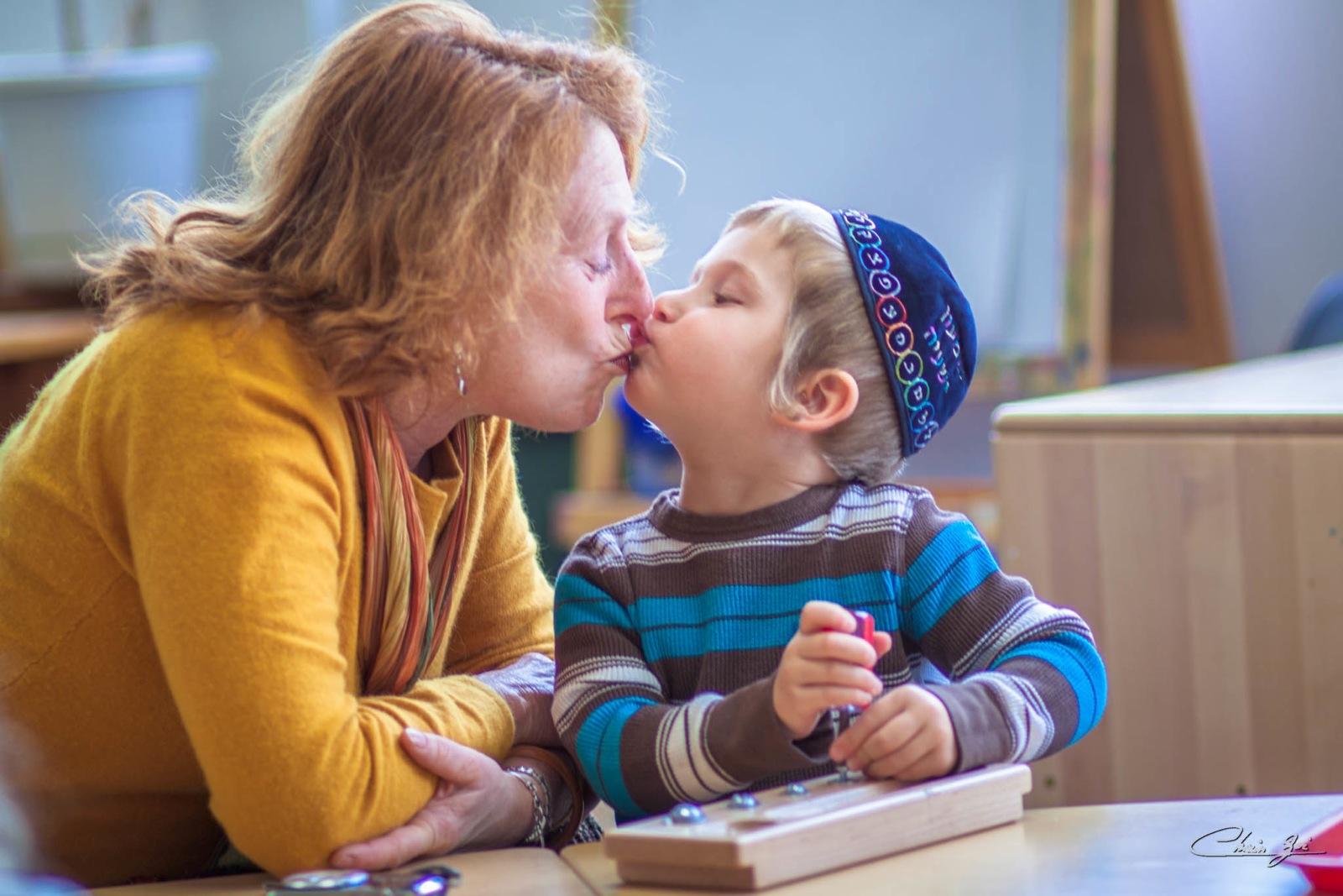 A woman and a small child wearing a kippah (yarmulke) kiss.