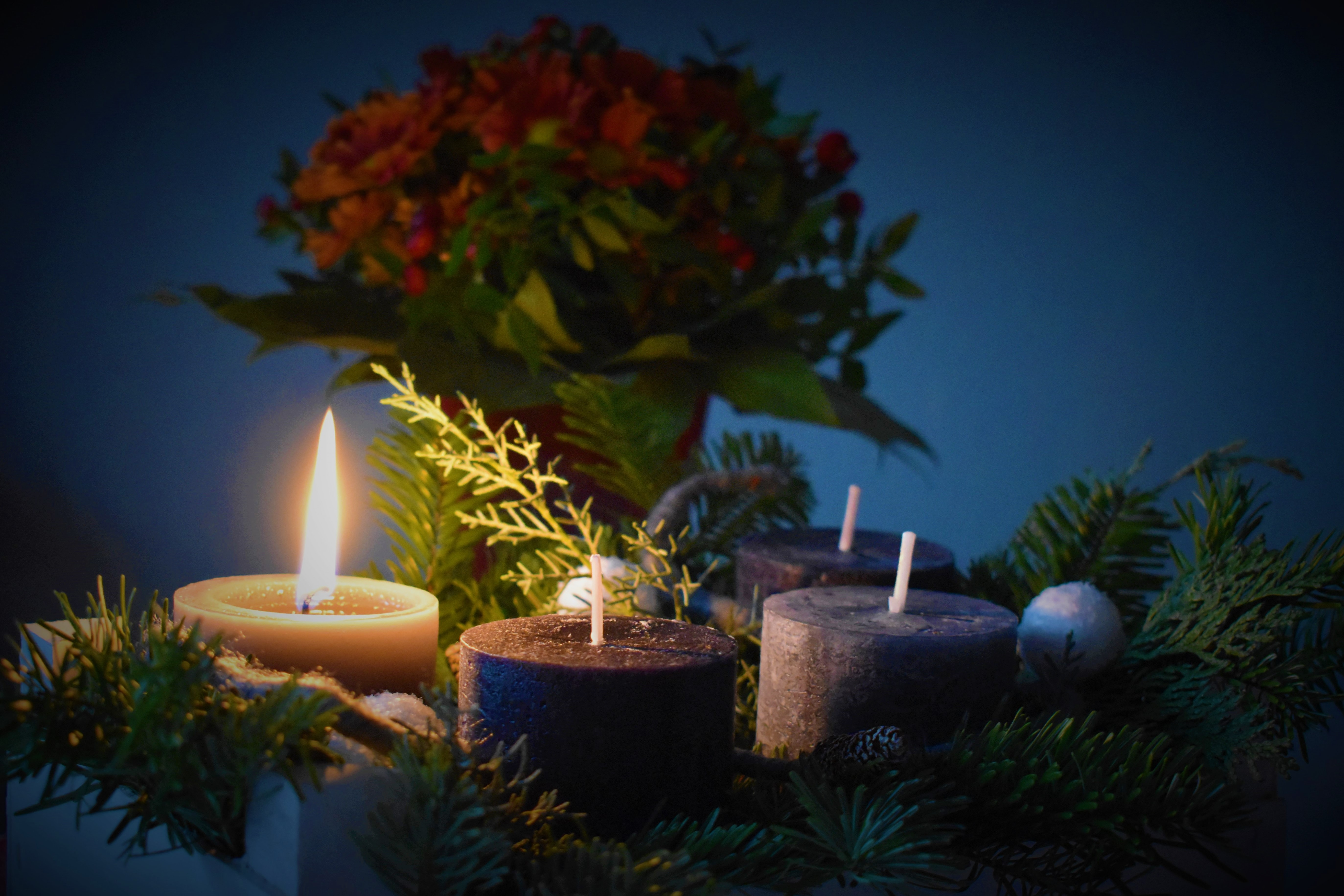 nestled into an evergreen wreath is a lit white candle and three unlit purple candles