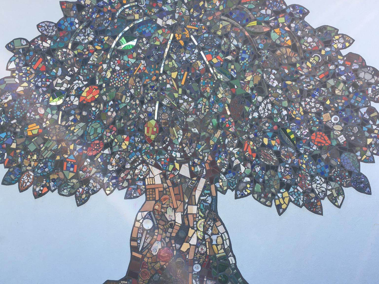 A mosaic--made with many pieces of broken glass--forming large tree.