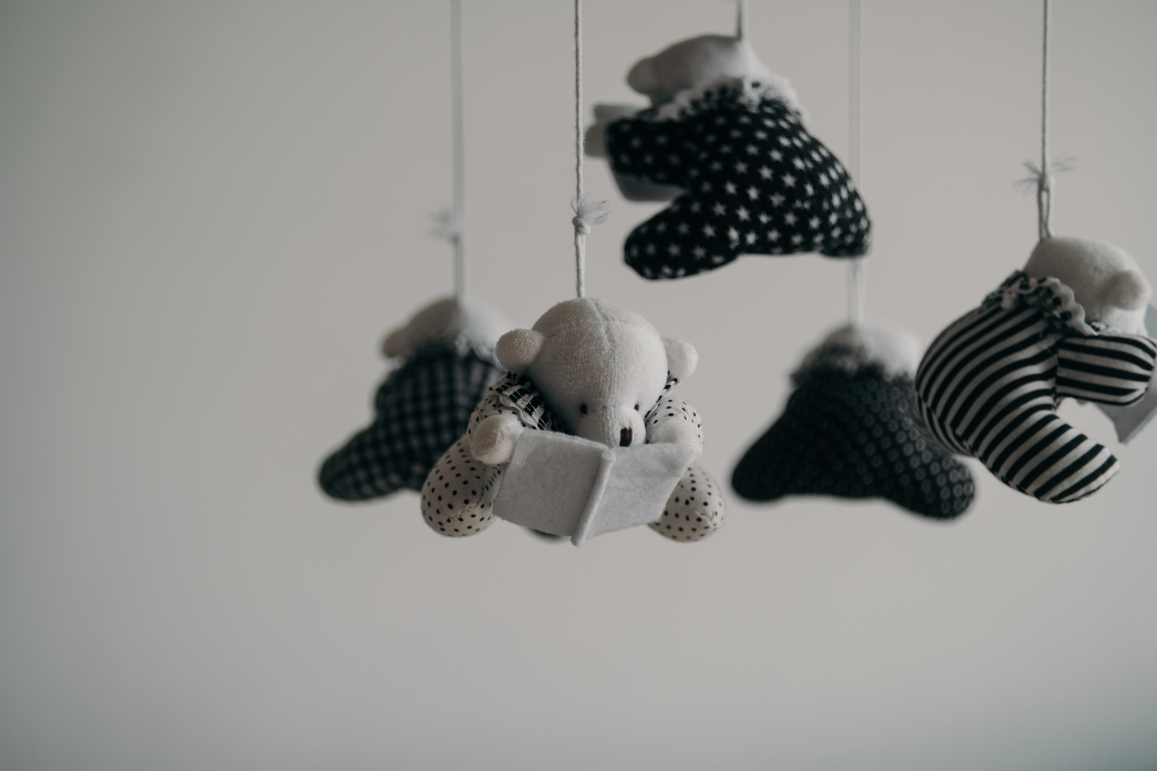 small fabric teddy bears, connected in a mobile, are suspended over an imagined baby's bassinet