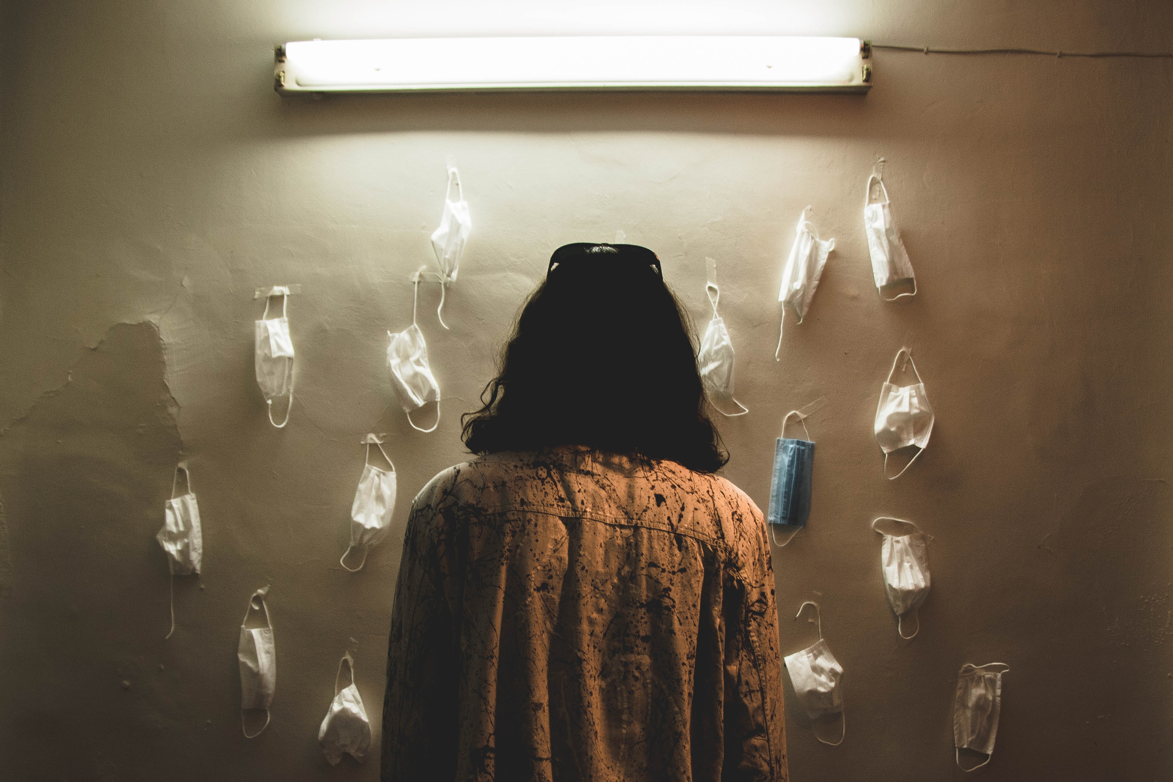The back of a person as they regard a wall, lit by a stark fluorescent light, on which many medical face masks are hung.