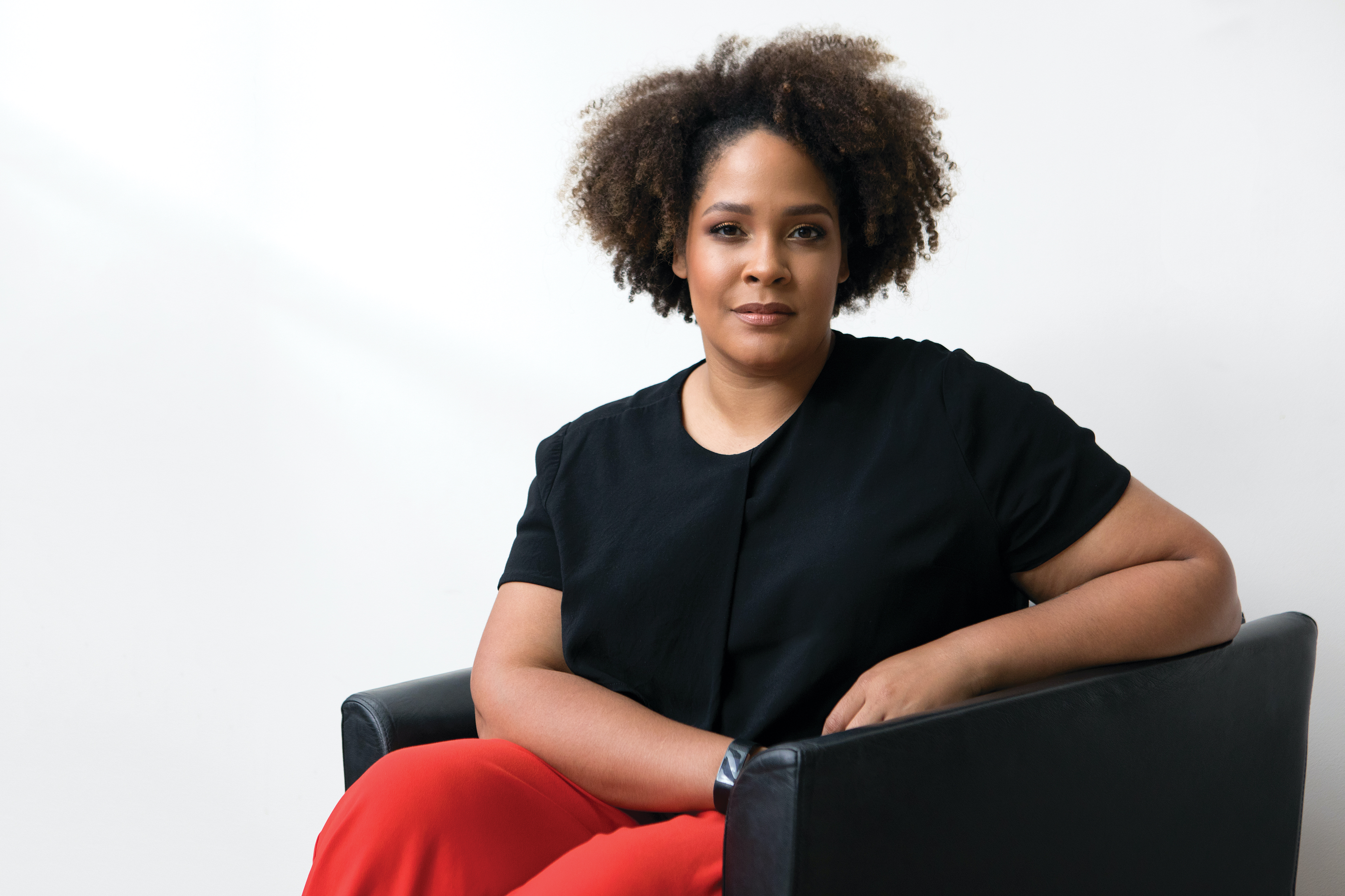 Ijeoma Oluo sits in a black leather chair, wearing a black shirt and red trousers.