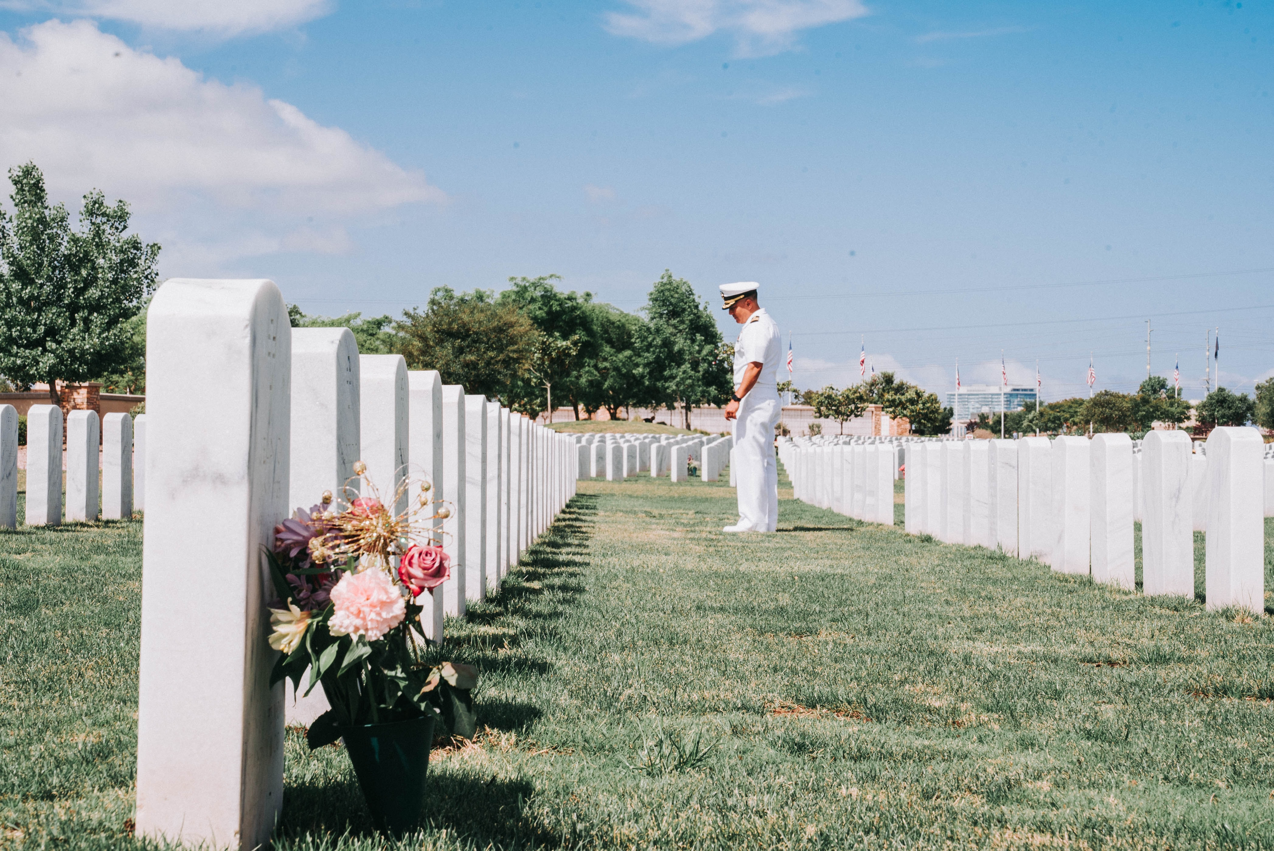A man in US Navy dress whites stands on the grass in a military cemetery looking at the headstones
