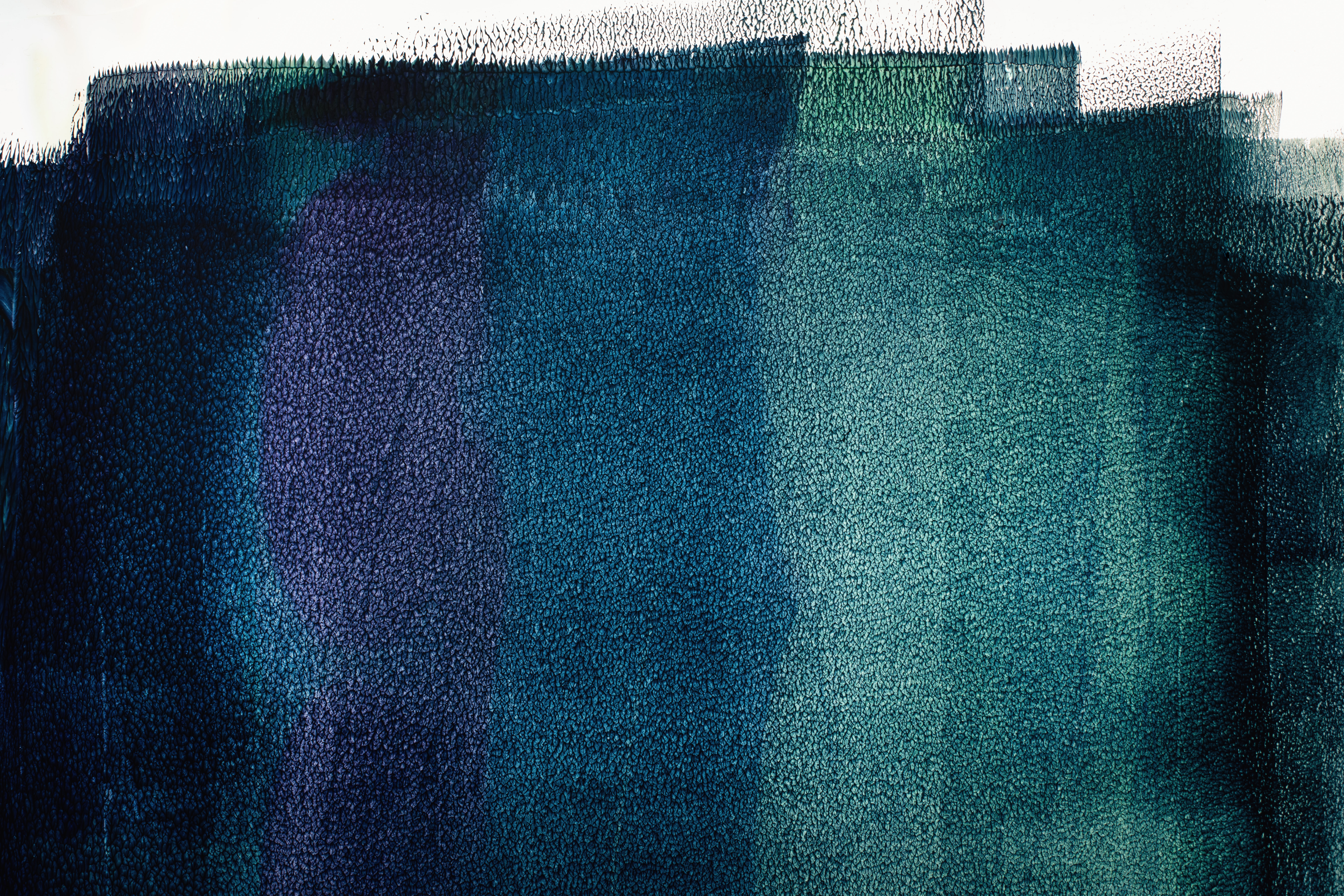 Vertical swaths of paint, in deep blues and indigos, on a wall.