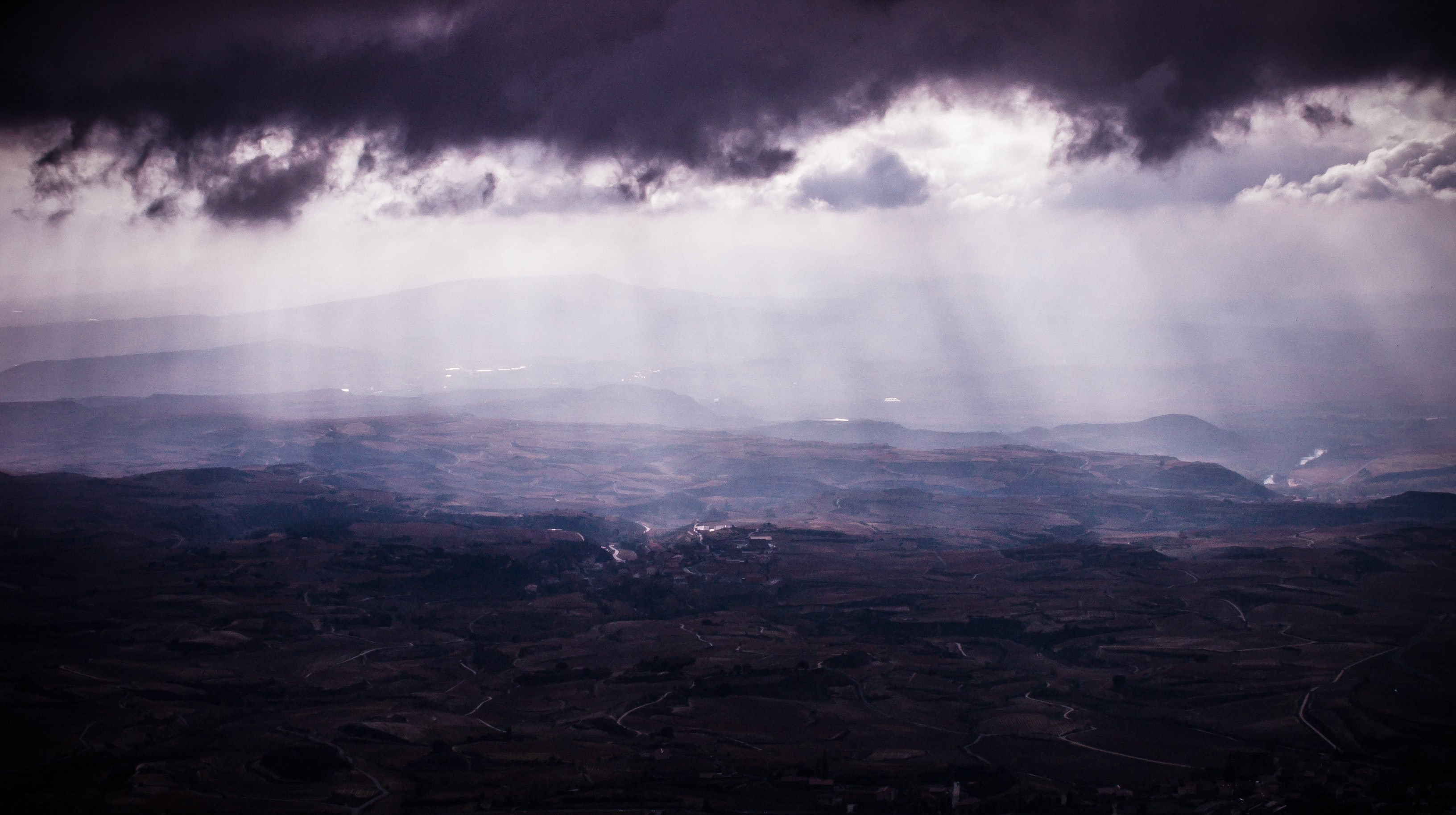 Sunbeams break through a layer of clouds over Rioja Alavesa, Laguardia, Spain, with rippling mountains stretching out.