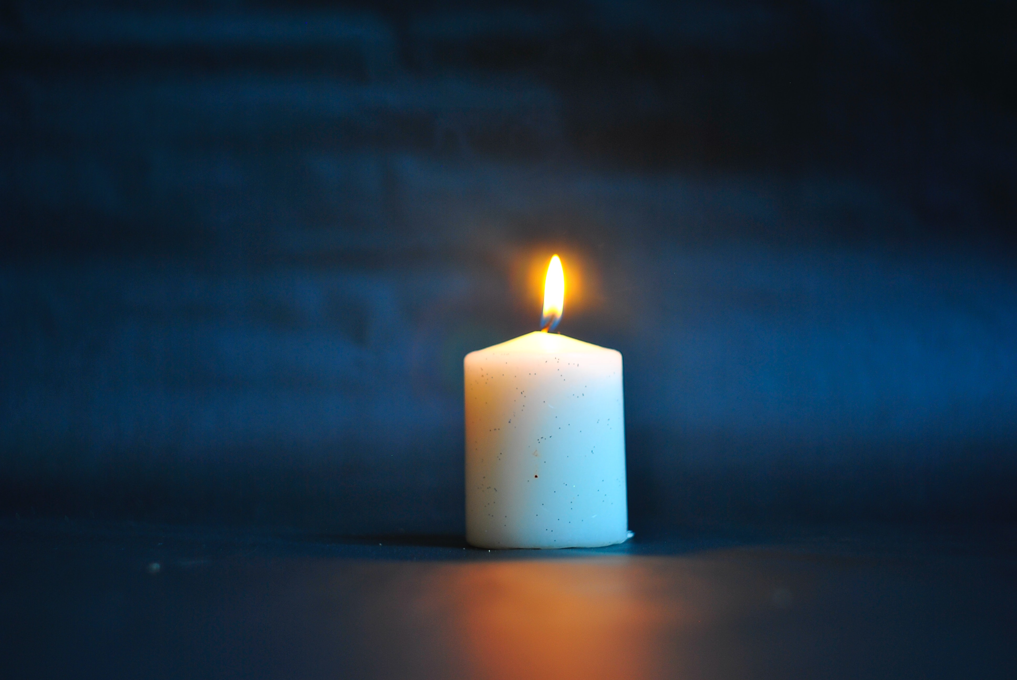 A white pillar candle is lit against a dark blue background.