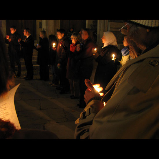 People bundled up against cold weather, standing outdoors in a circle with lit candles in a vigil. Photo by Adam Gerhardstein/UUA.