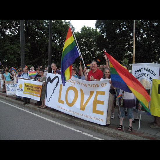 People standing alongside a road, holding rainbow flags and banners reading things like 'Standing on the Side of Love' and 'PFLAG: Supporting families and safe schools.' Photo by Morgan McLean.