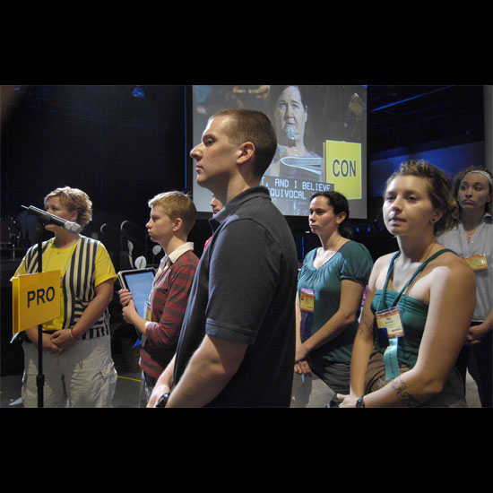 Youth and young adults stand at the 'Pro' microphone during a Plenary debate, listening to the woman speaking at the 'Con' microphone. Photo by Nancy Pierce.