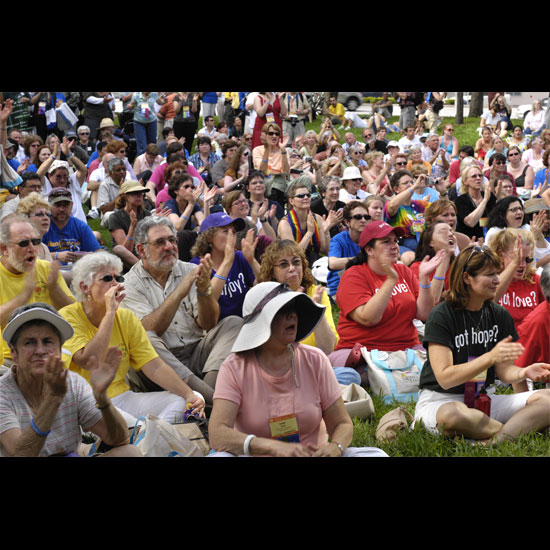 A crowd of Unitarian Universalists, sitting on the grass, clapping and calling out. Photo by Nancy Pierce.