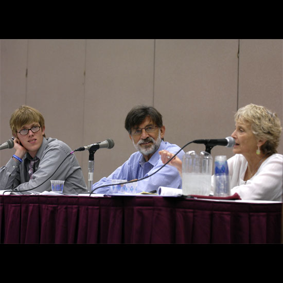 Three panel members sitting at their table; one speaking into a microphone. Photo by Nancy Pierce.