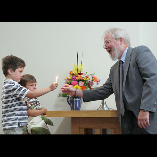 Two children pass a lit candle to Brian Griffin, for lighting the chalice on the table beside them. Photo by Karen Krogh.