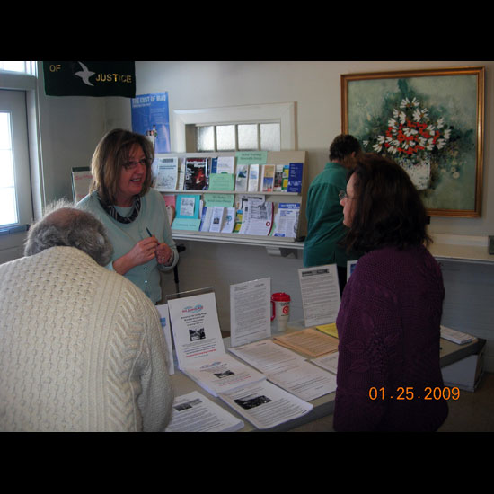 Susan Leslie helps other Unitarian Universalists at an information display about Living Wage Days. Photo courtesy Susan Leslie.