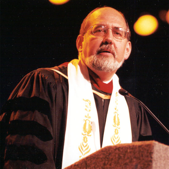 John Buehrens, speaking at a microphone in his ministerial robes. Photo by Nancy Pierce.