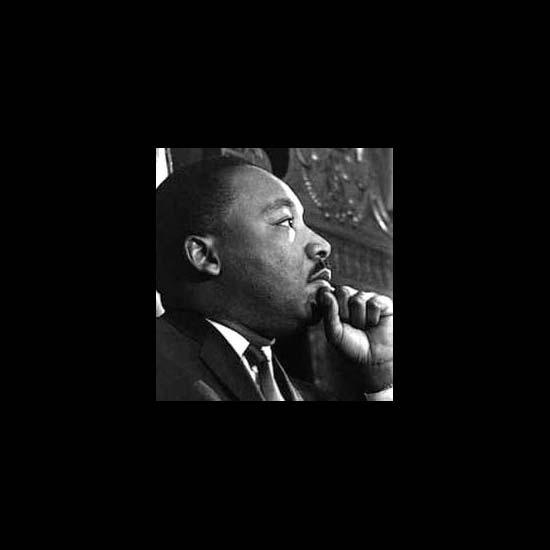 Dr. Martin Luther King, Jr. with his hand to his chin, listening.