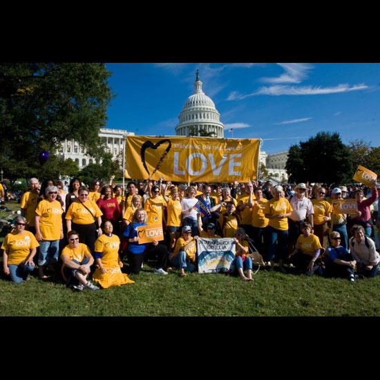 A crowd of people wearing 'Standing on the Side of Love' (SSL) t-shirts gathered in front of the U.S. Capitol, holding up a large SSL banner and several smaller signs. Photo courtesy the Standing on the Side of Love Campaign.