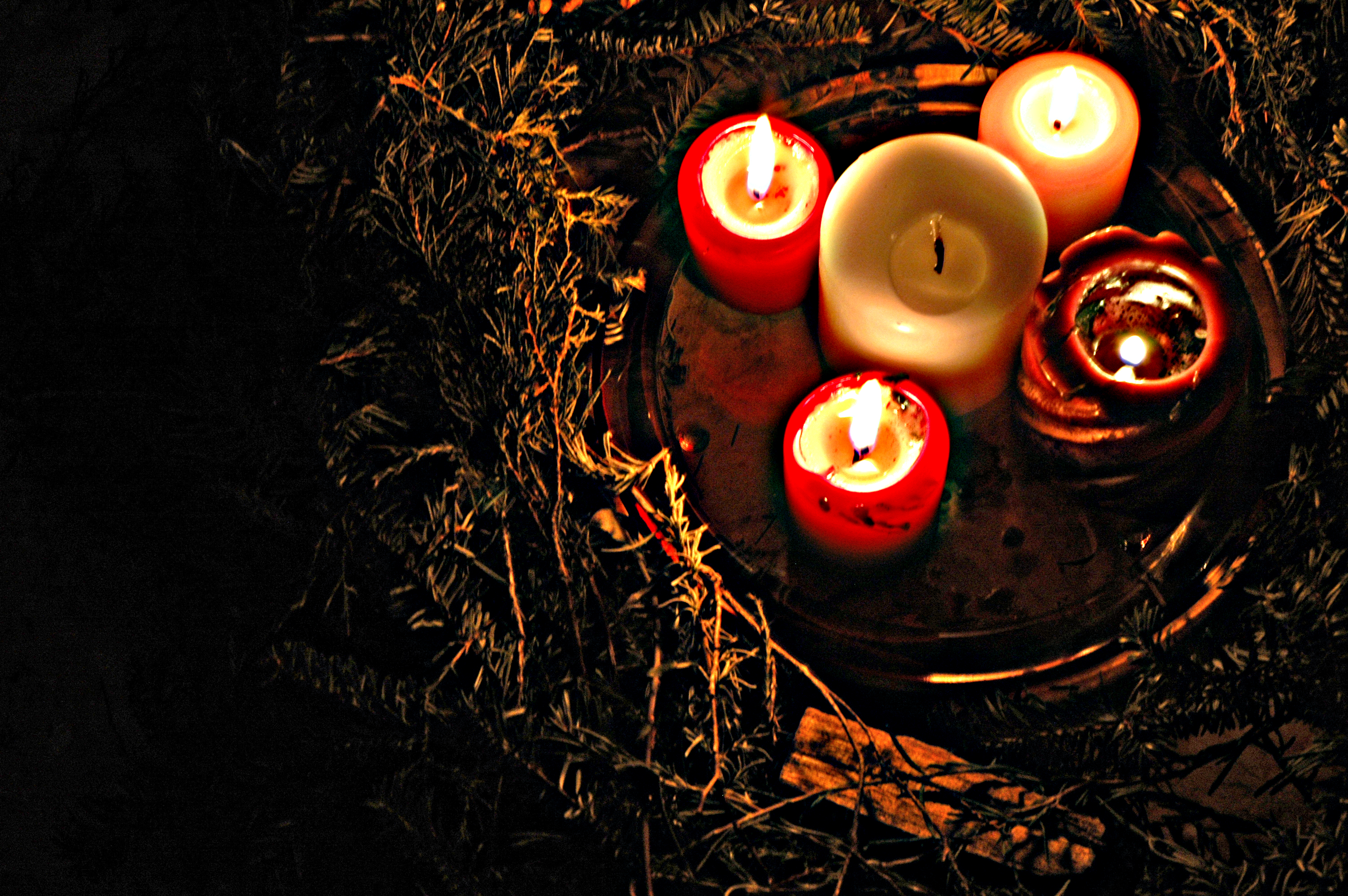 From above, an arc of a thick evergreen wreath. In its center, four red pillar candels are lit; the white pillar candle at the center is unlit.