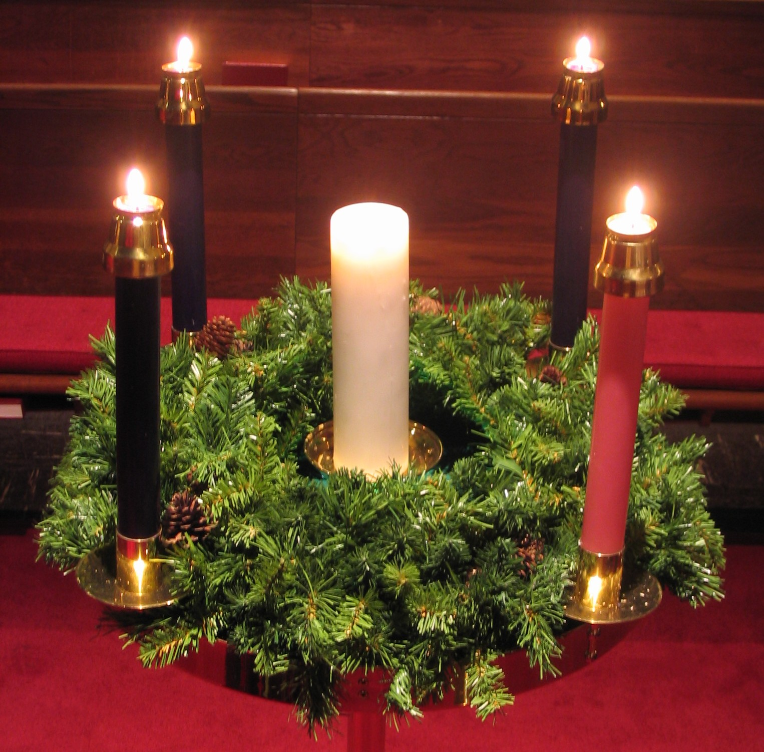 An Advent wreath, with four lit candles, and a fifth white candle in the center