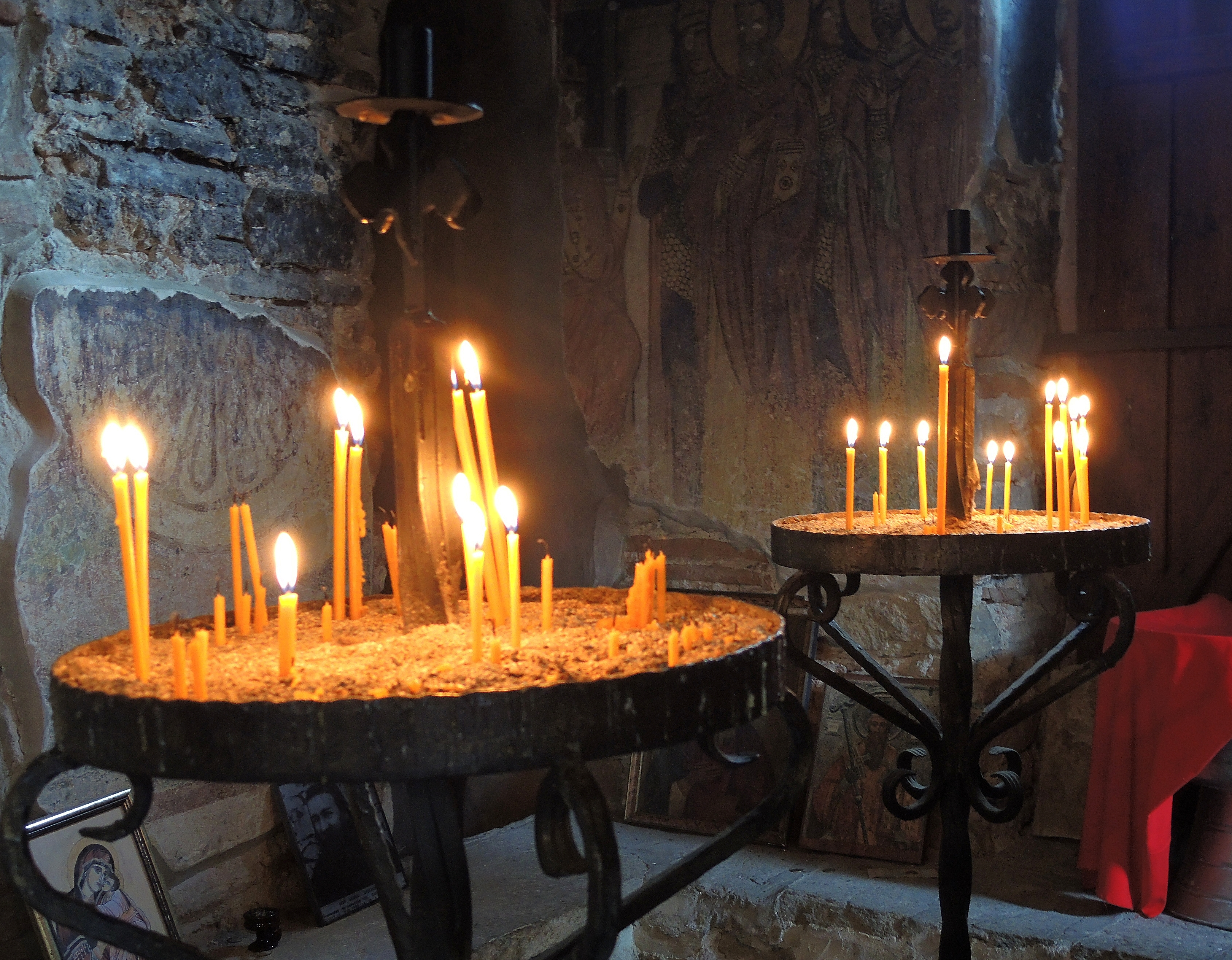 In front of stone walls, two round trays hold an array of slim, lit candles