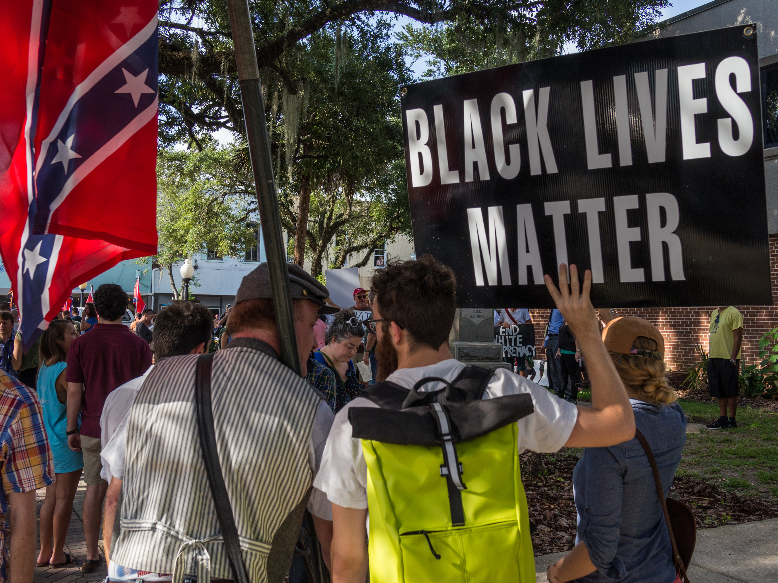 Behind a crowd of protesters, one man holds a Confederate flag while anothr holds a