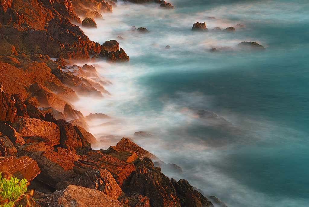 Foamy waves wash up on craggy rocks, made red by the sun, in Morrazo, Galicia (Spain)