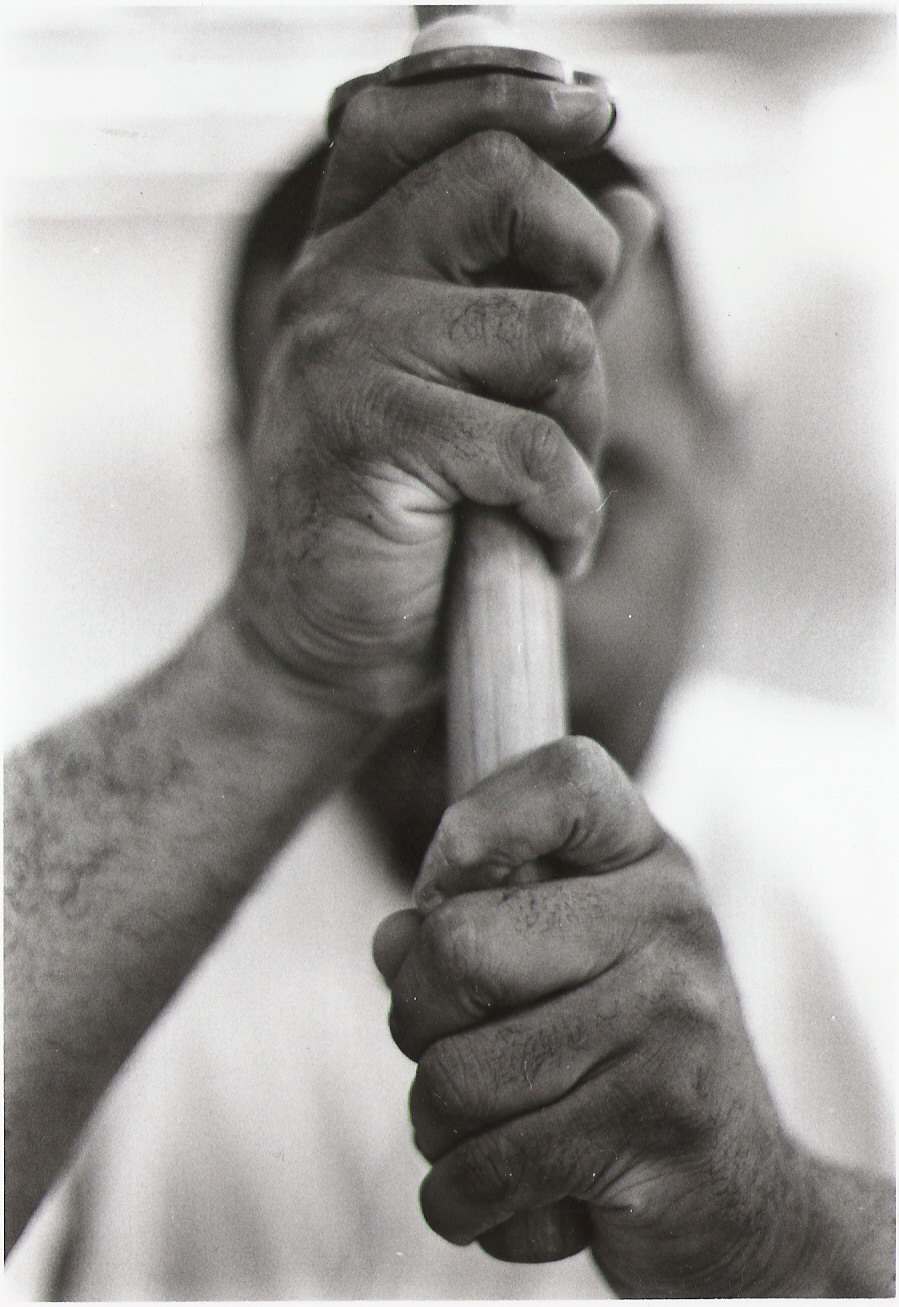 Close-up of a man's hands gripping a handle, his face obscured.