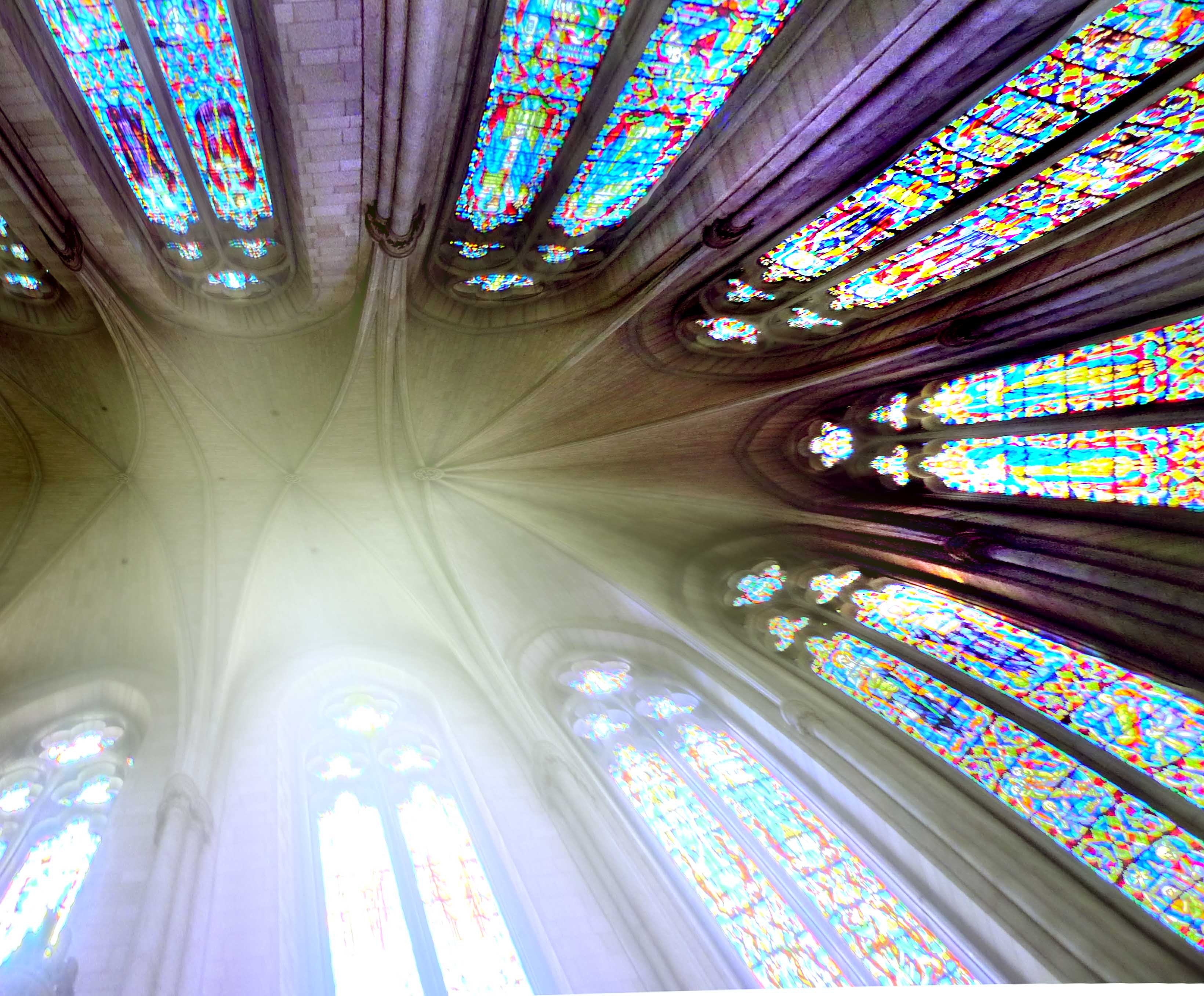 a view up from the floor of a cathedral to the ceiling, with stained glass windows on all sides