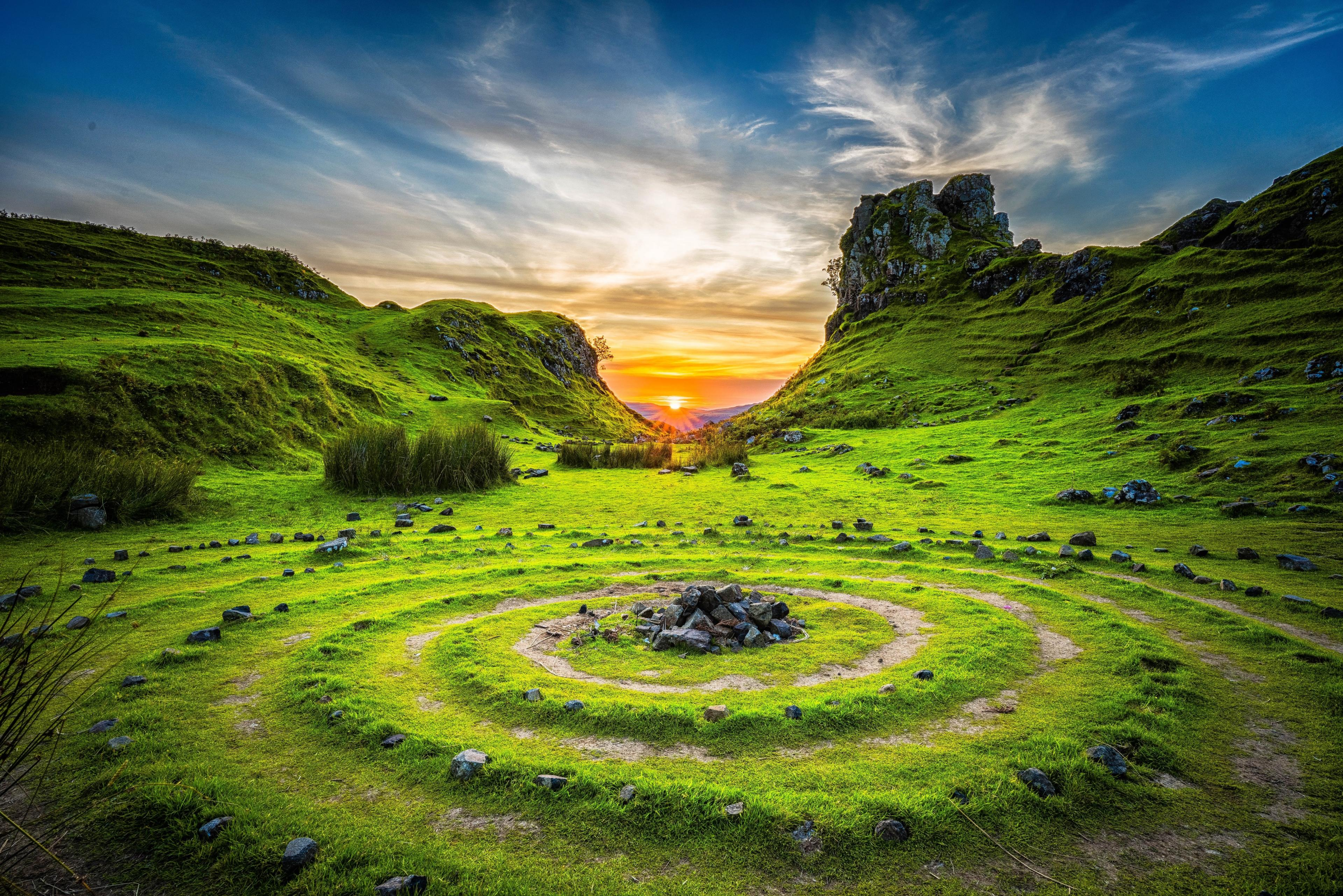 The sun rises between two green hills. In the foreground, circles of stone and earth radiate outward from a stone center.