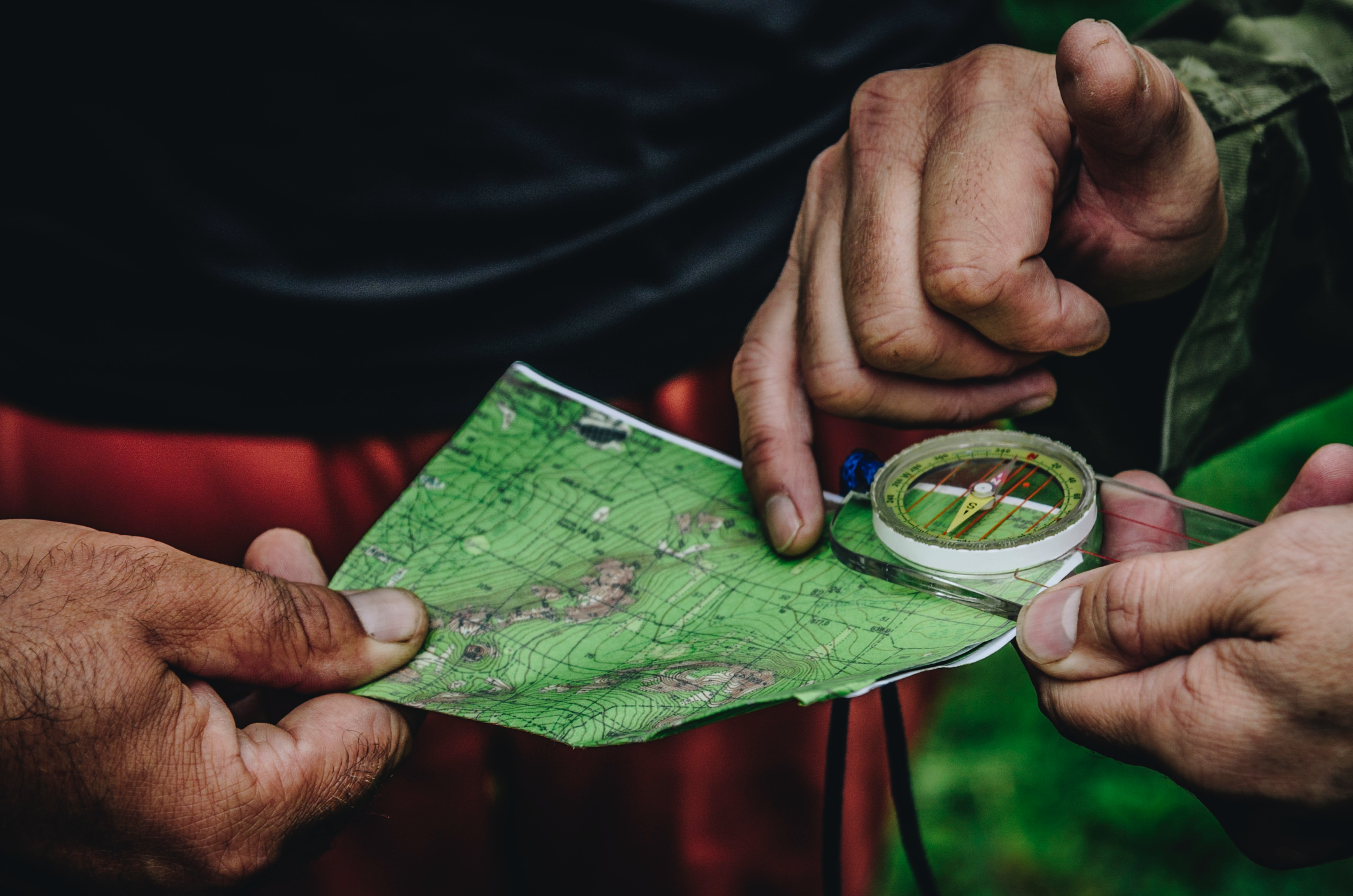 Two pairs of hands hold a map and a compass, as if to get bearings mid-journey.