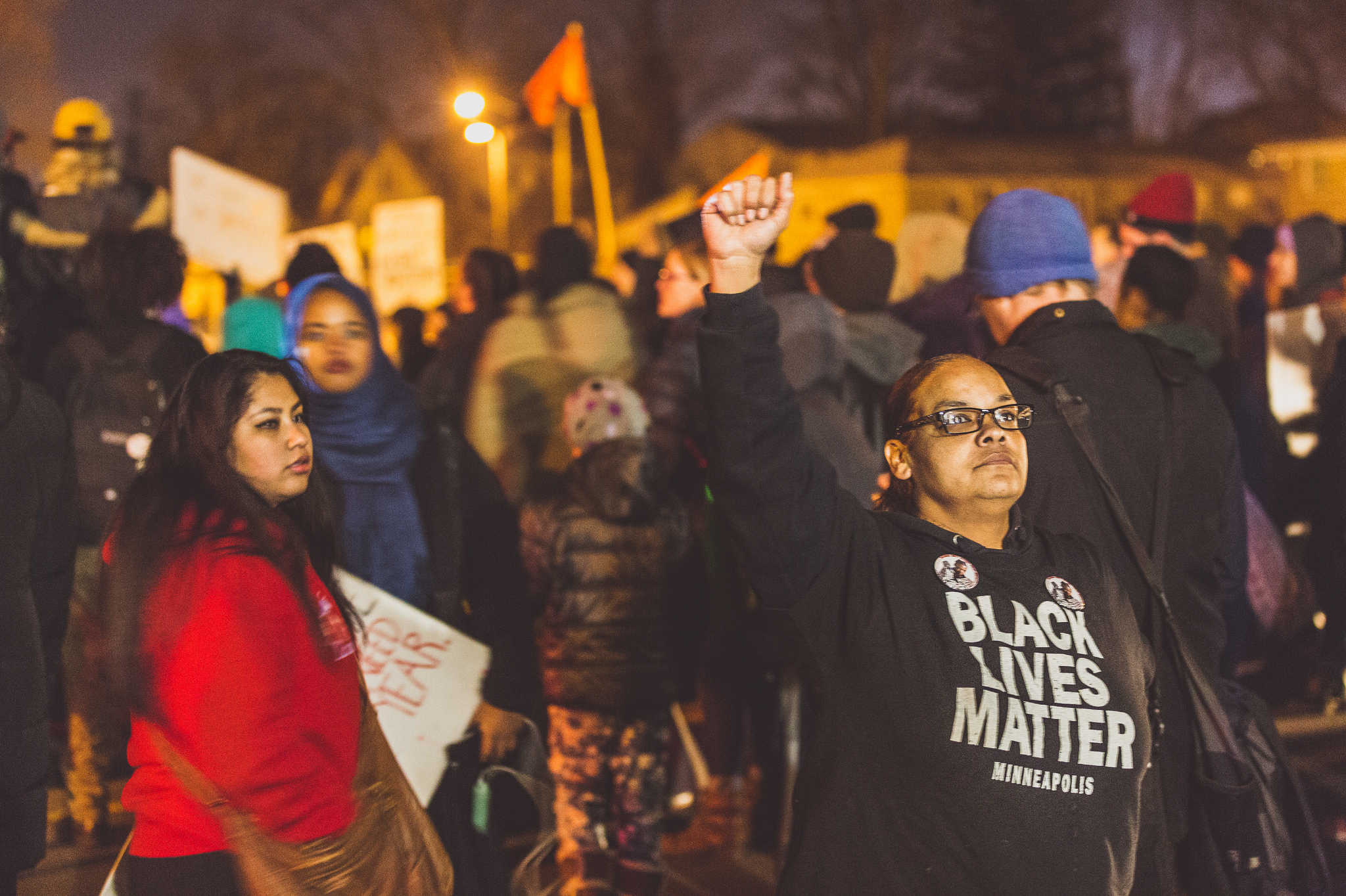 In front of a nighttime crowd, holding signs, a woman in a Black Lives Matter sweatshirt raises her fist into the air.