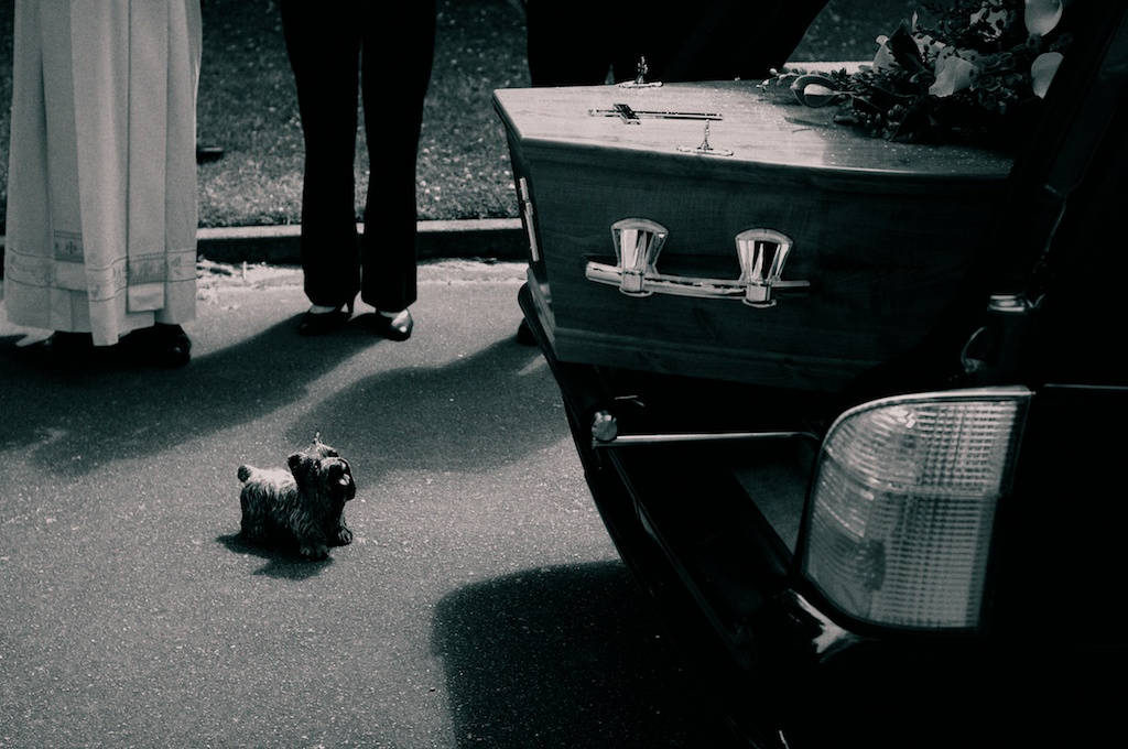 the end of a coffin extends from a hearse, with the feet of a mourner and priest nearby