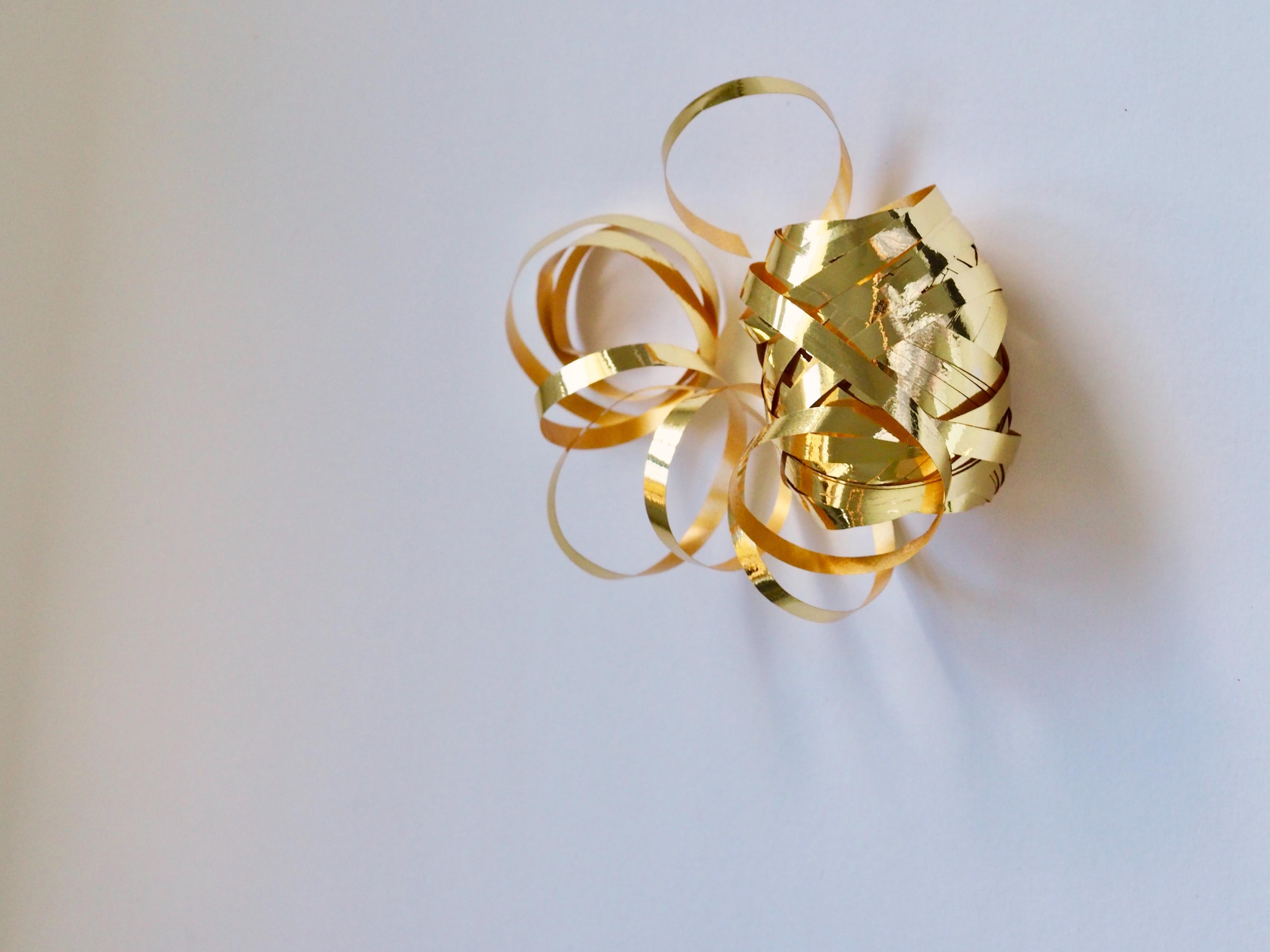 A spool of metallic gold ribbon, as would be used to tie around a holiday gift.