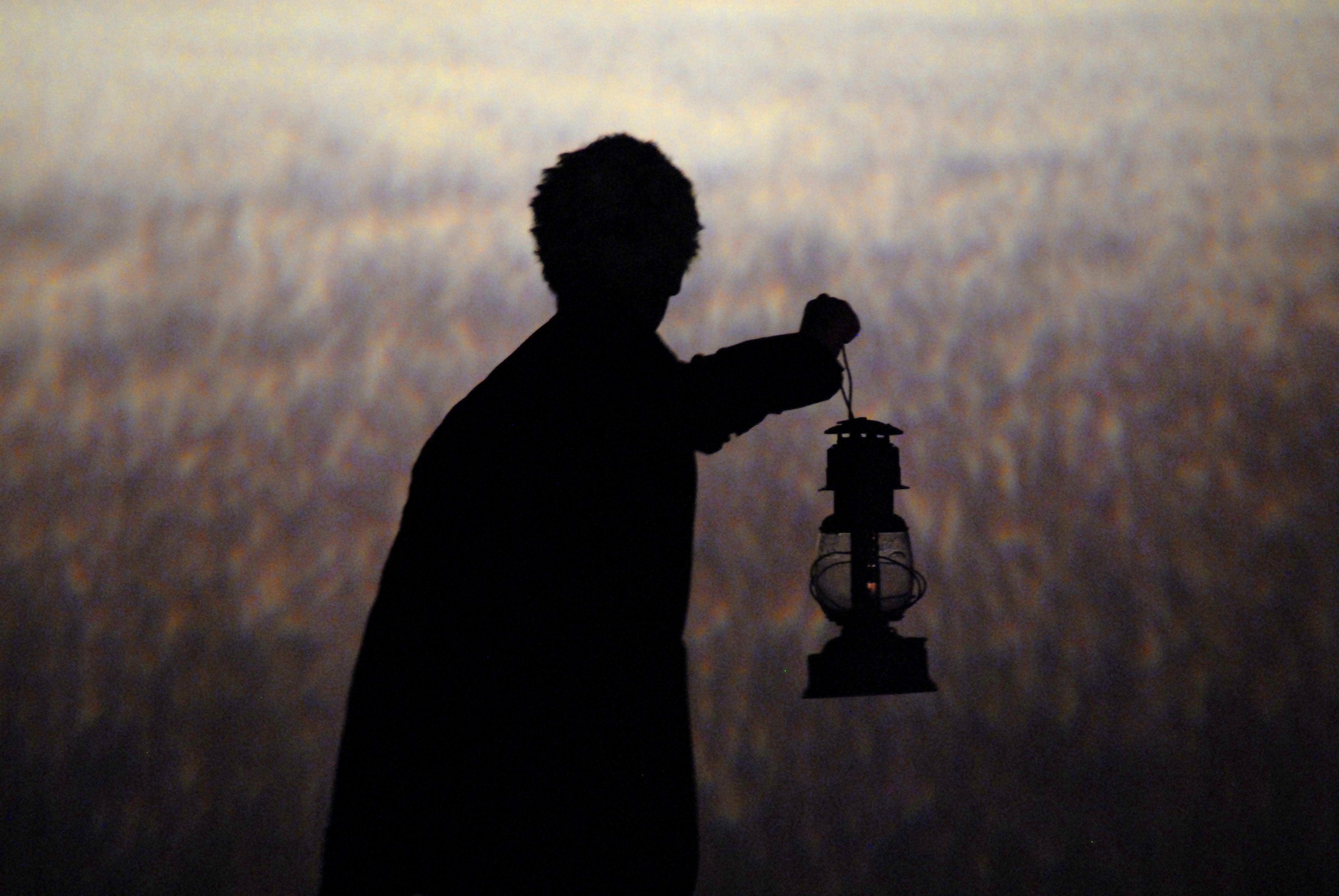 In front of a wheatfield backdrop, the silhouette of a person holding up an old-fashioned lantern (from a 2011 production of