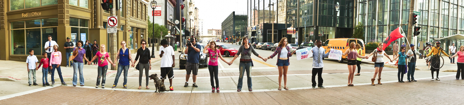 a line of people, of all ages, facing the camera and holding hands, across the intersection of an empty city street