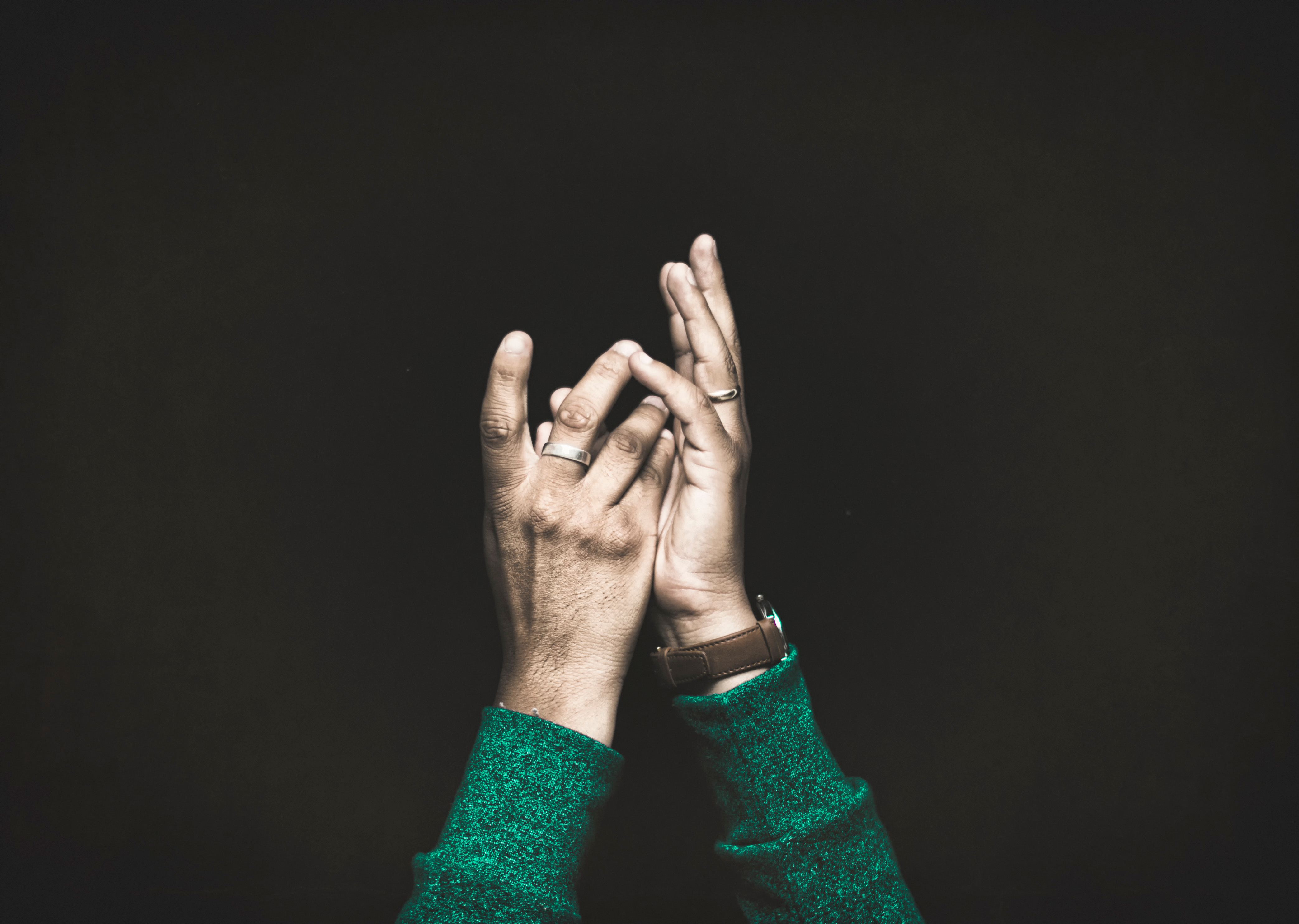 Against a black backdrop, a person's hands reach gracefully toward the sky.