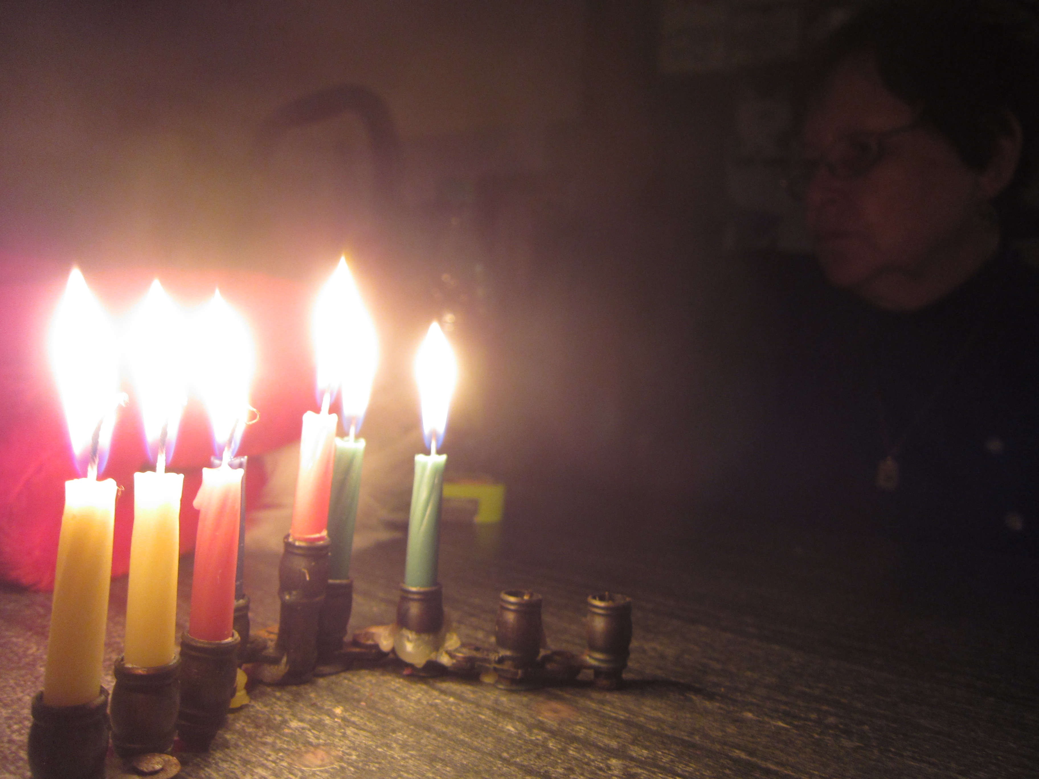 A small menorah with six lit candles, with a person's face obscured in the dark background