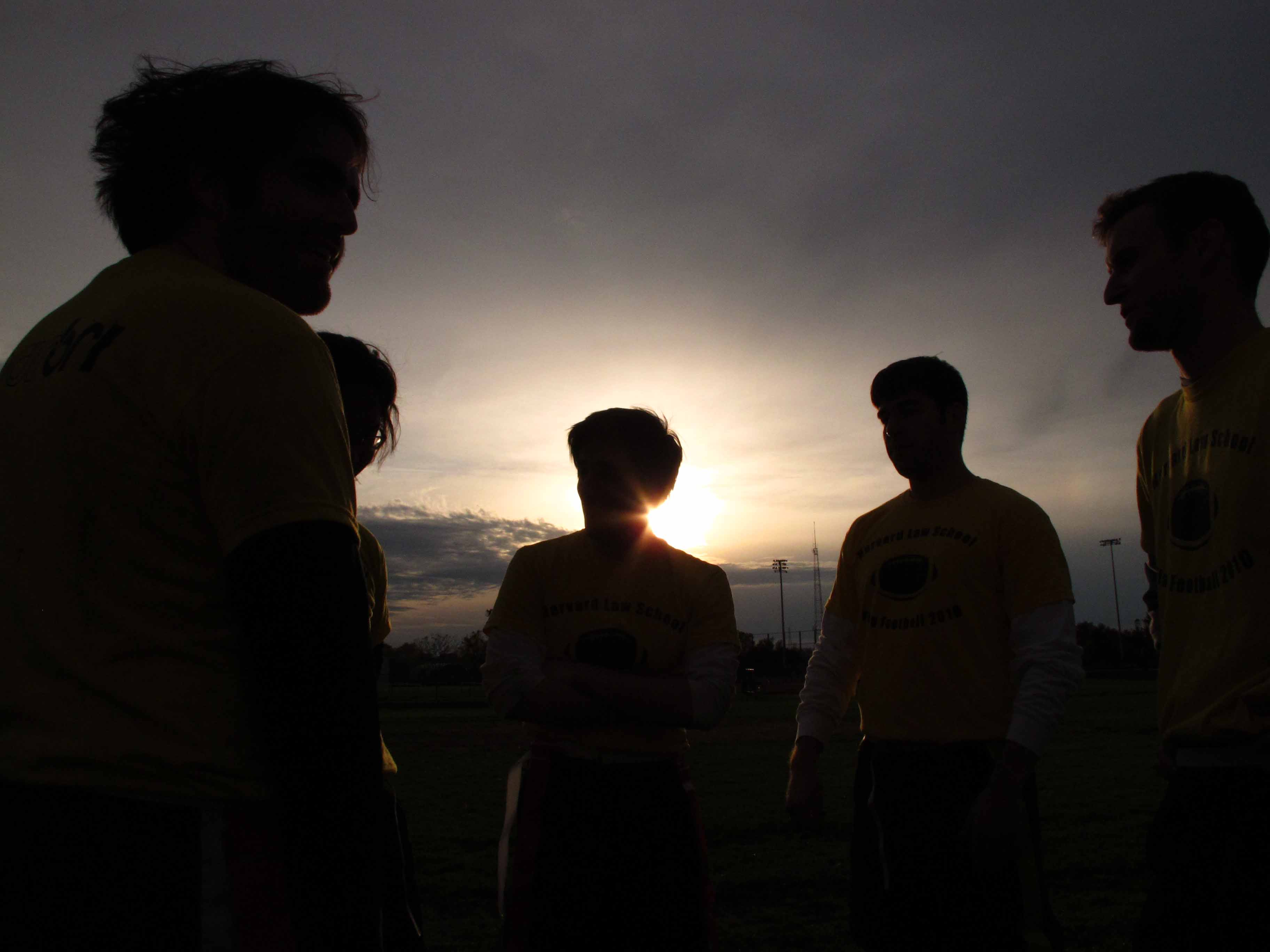 Against a setting sun, five people form a circle, visible only as silhouettes