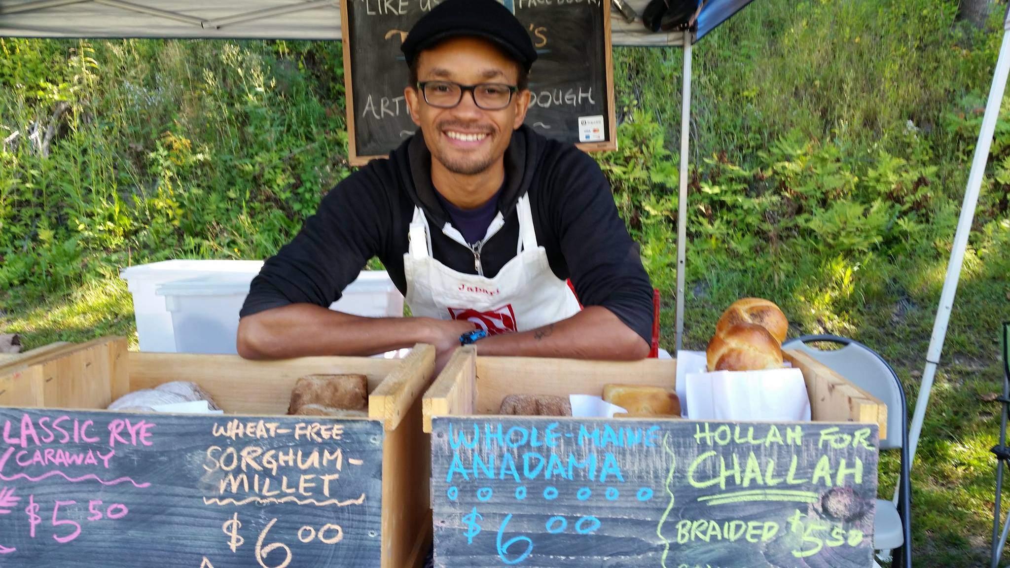 Jabari Jones smiles as he leans over crates filled with fresh bread, at the farmer's market.