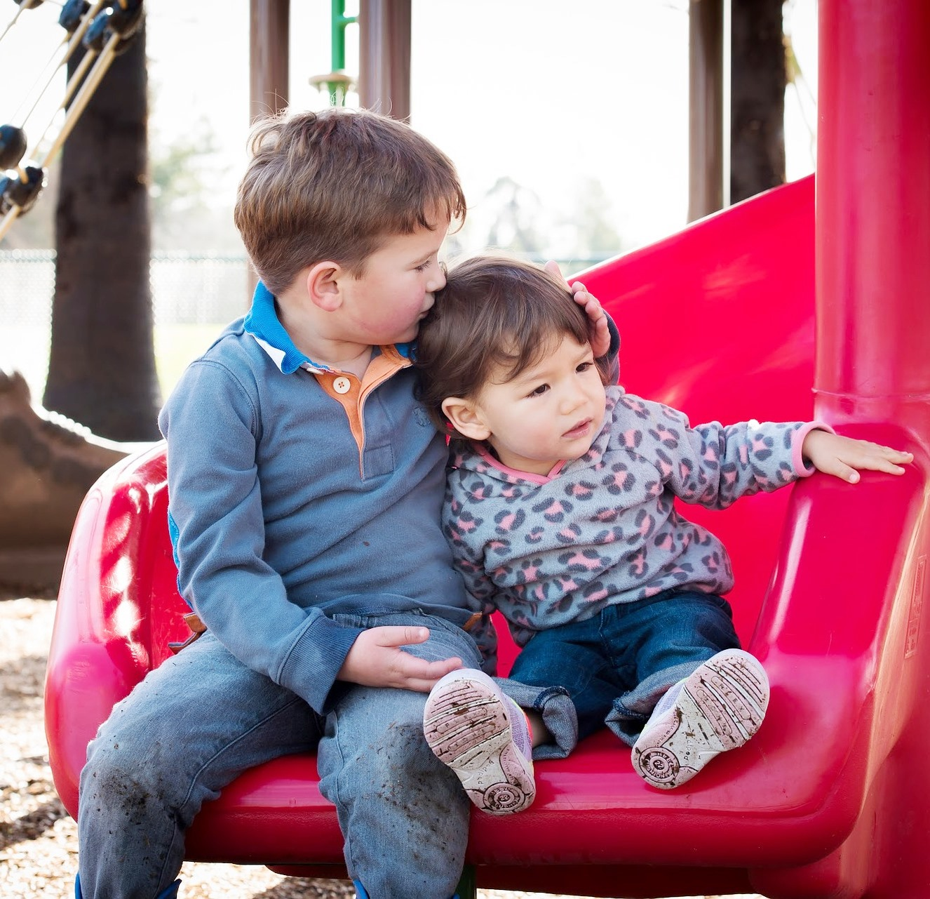 Two young children hugging at the bottom of a playground slide