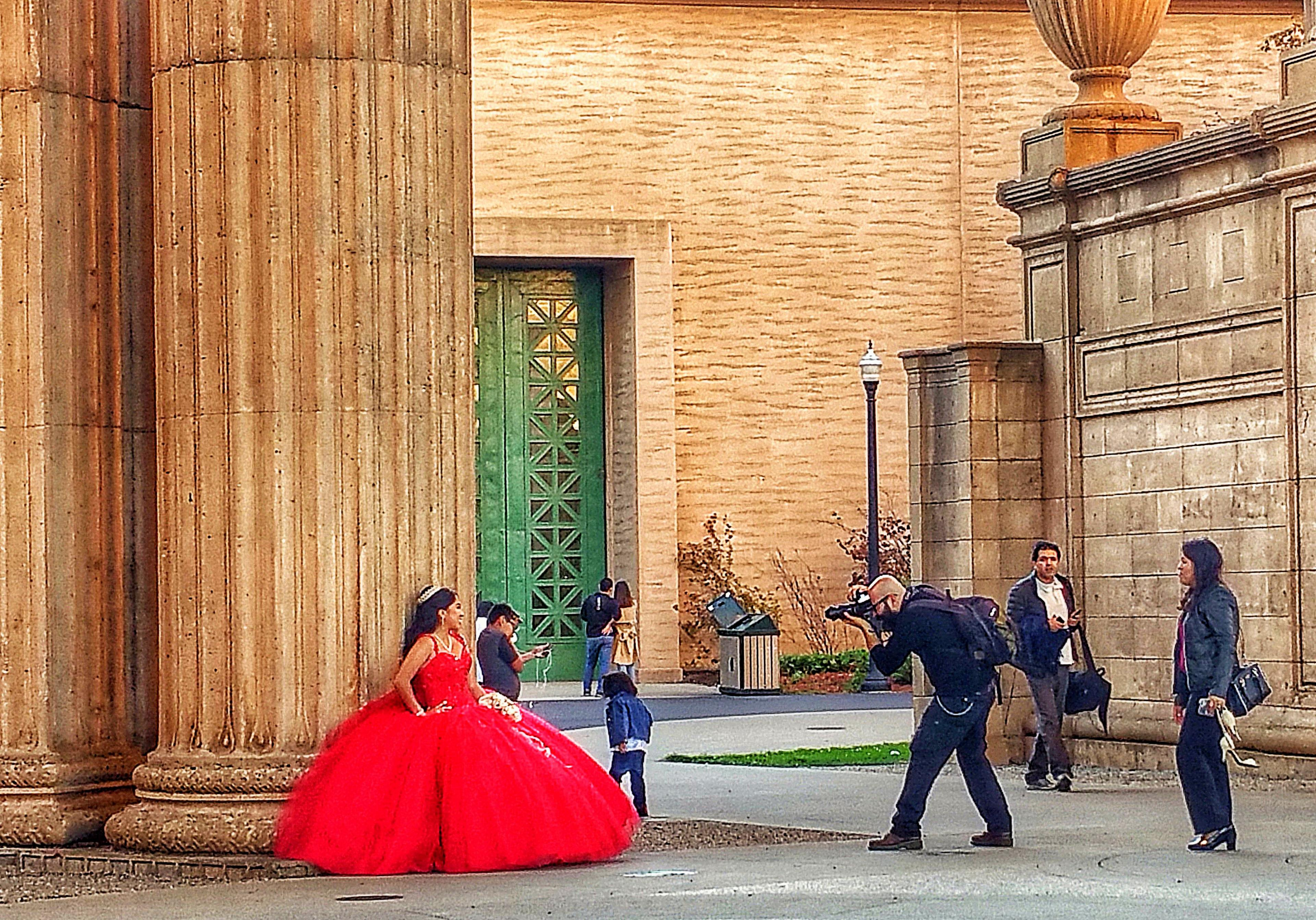 A team of professional photographers, outdoors, takes photos of a quinceañera in a billowing red formal gown.