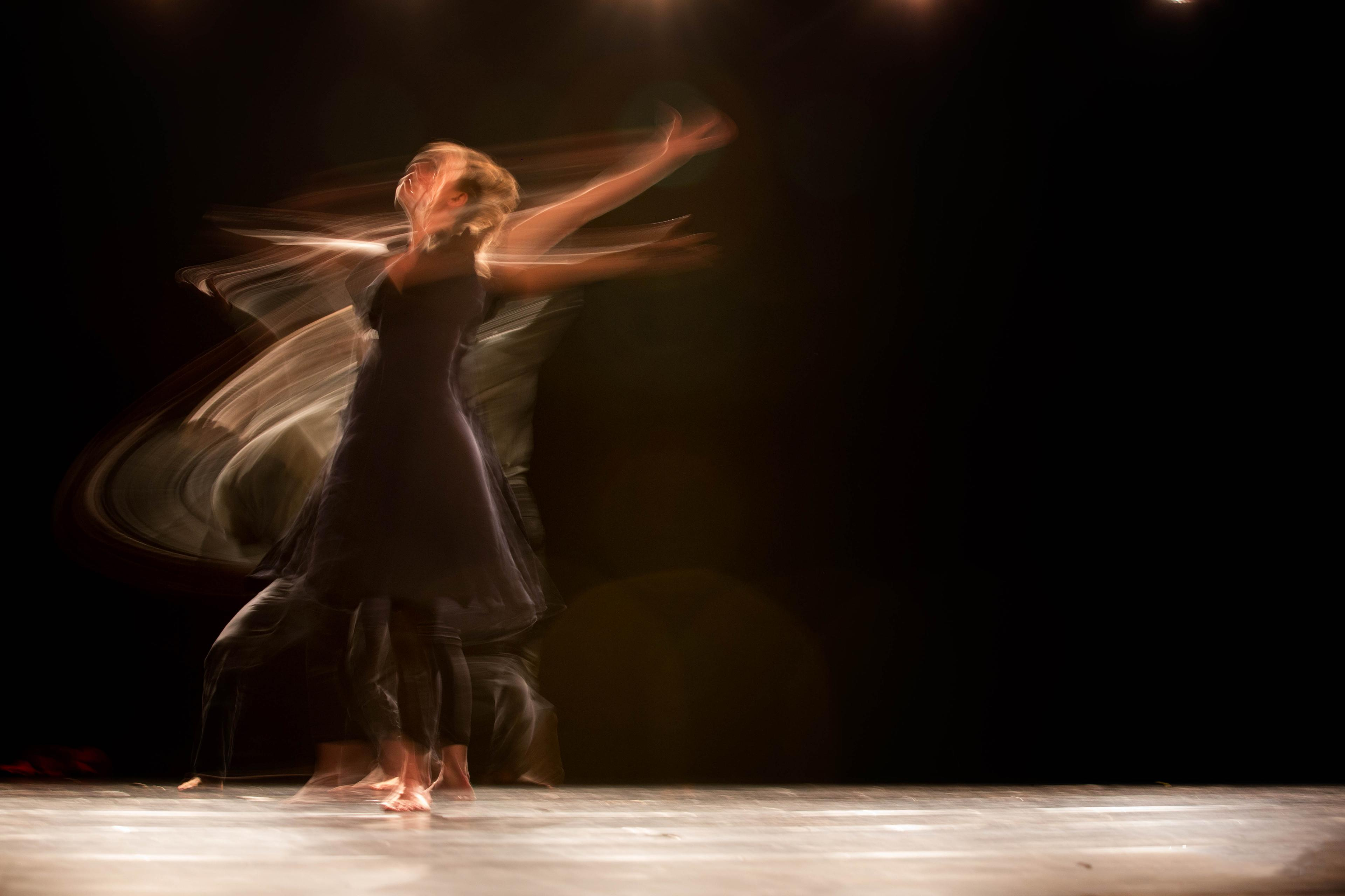 A time-lapse photo showing graceful, dance-like movements of a person against a black background