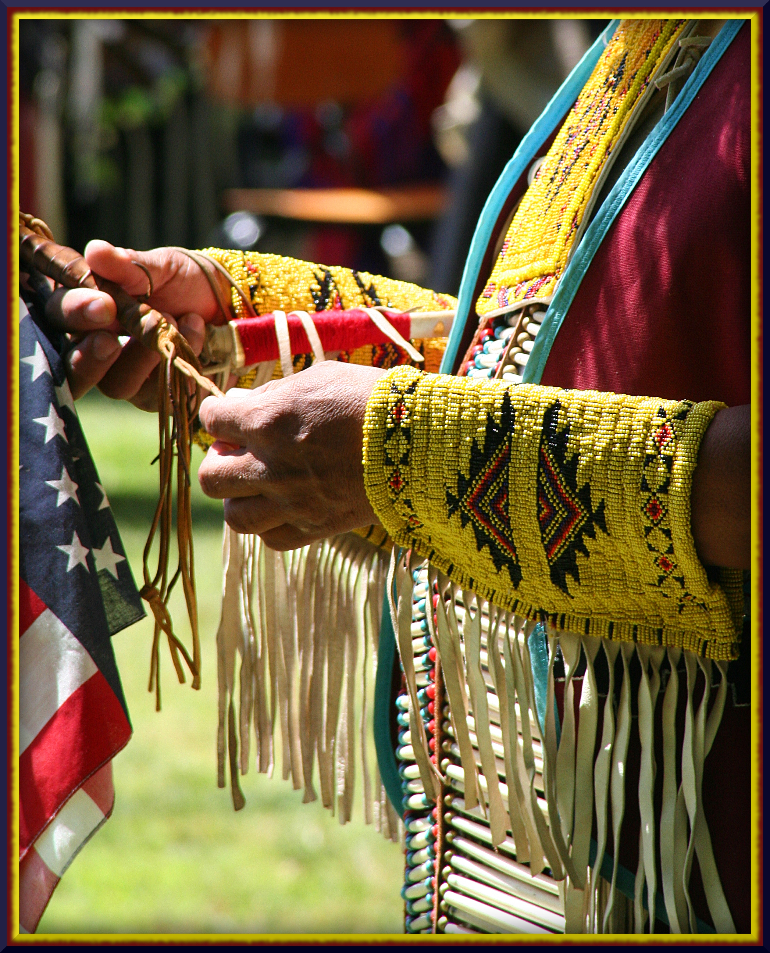 The arms, hands and chest of a Native American are visible, in traditional garb, but the person holds a small American flag.