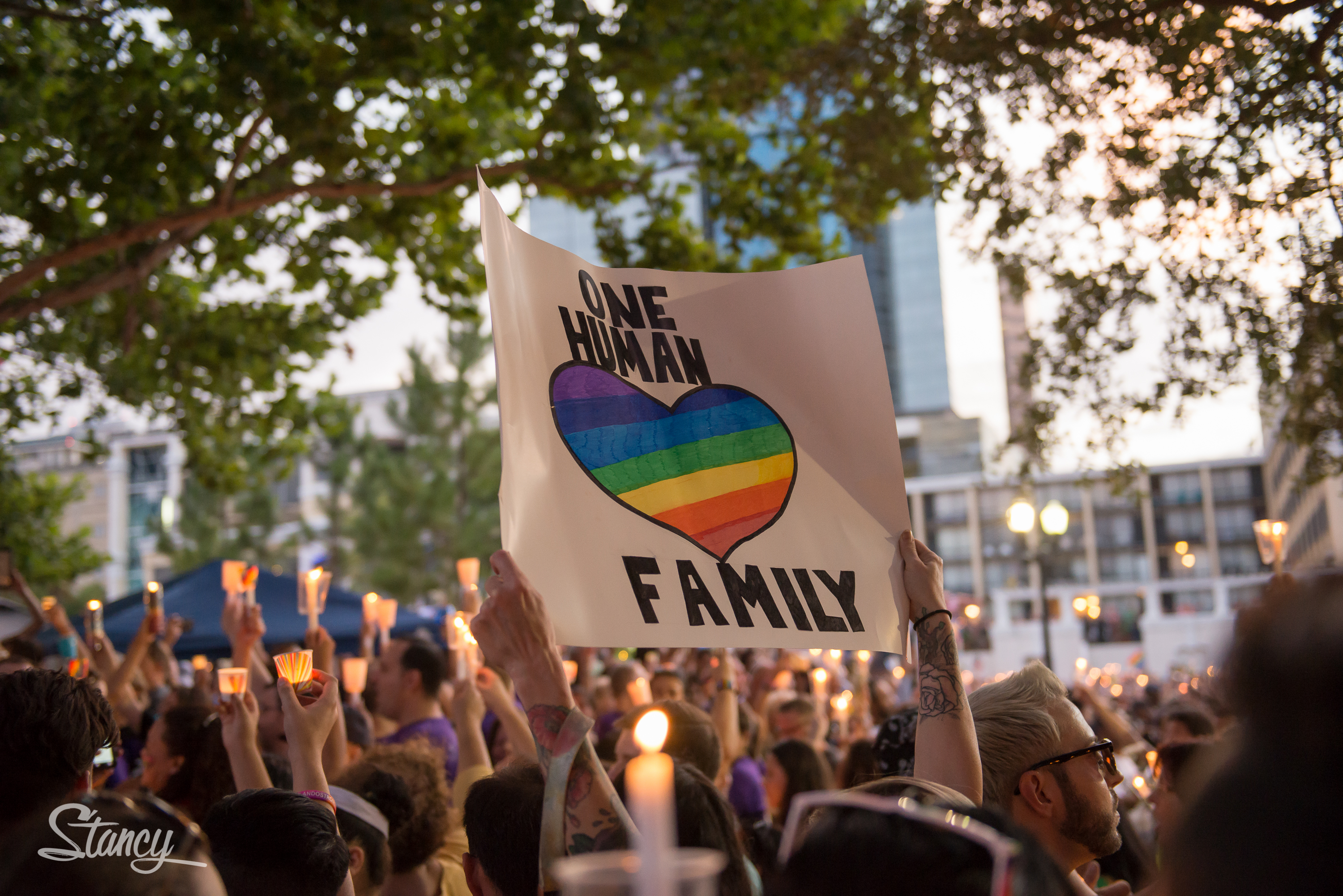 Above a sea of hands holding lit candles in the air, someone holds a sign with a rainbow heart: