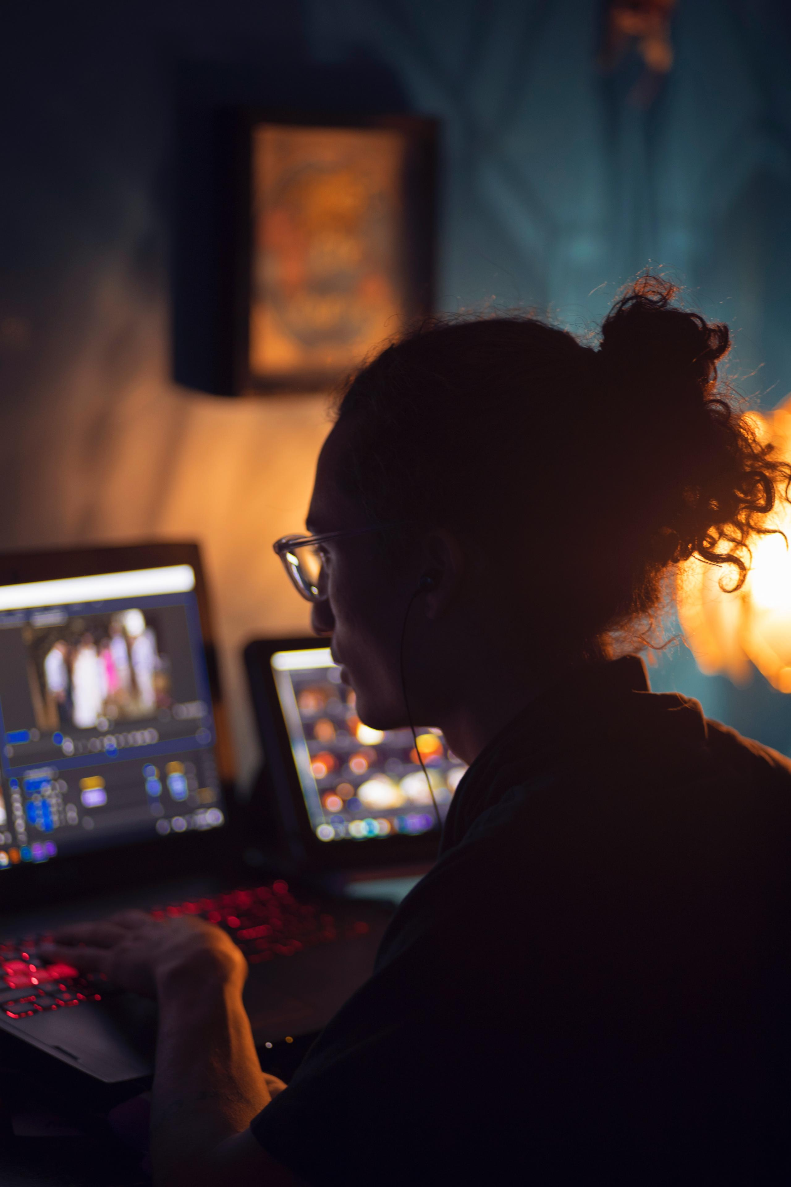 A person wearing glasses, with curly hair tied back, sits in front of two computers with colorful images on their screens.