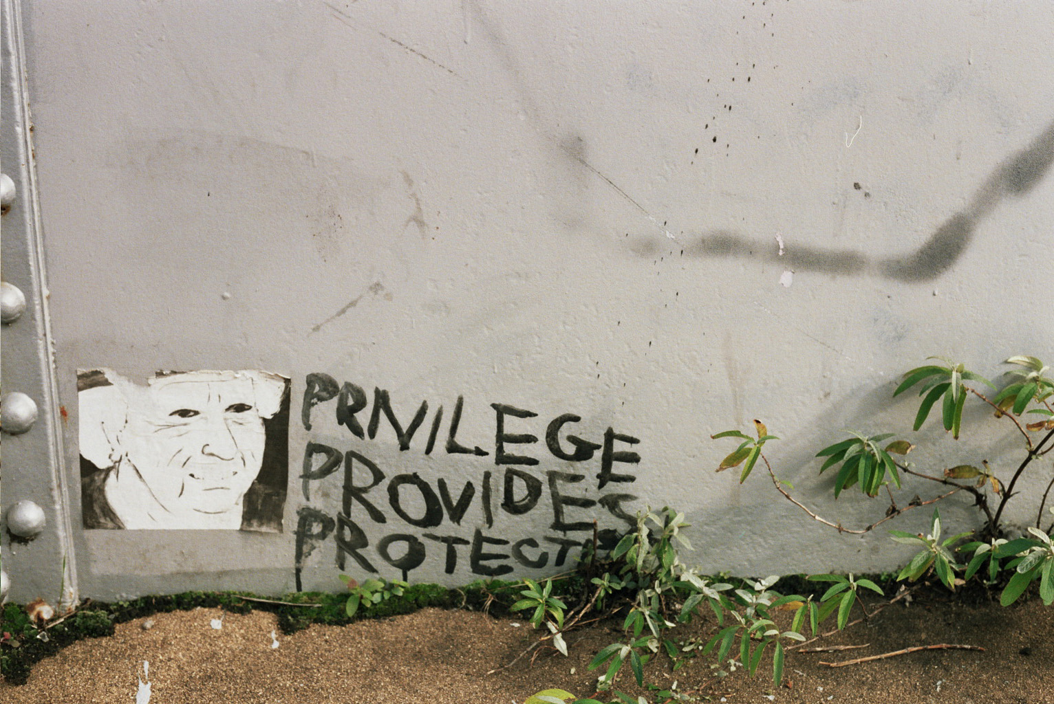 At the bottom of a wall, three words are painted: privilege provides (+) protects