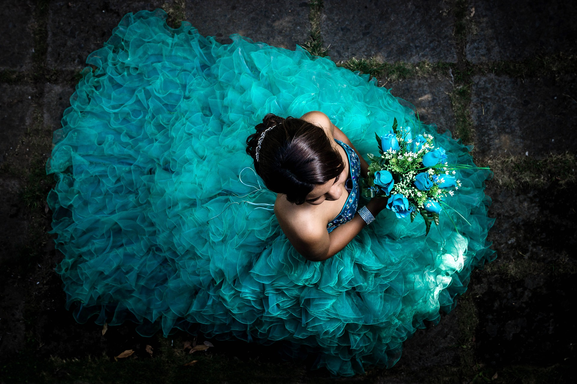 A Latina girl in a full, formal teal gown, and holding a bouquet of turquoise flowers, shot from above.