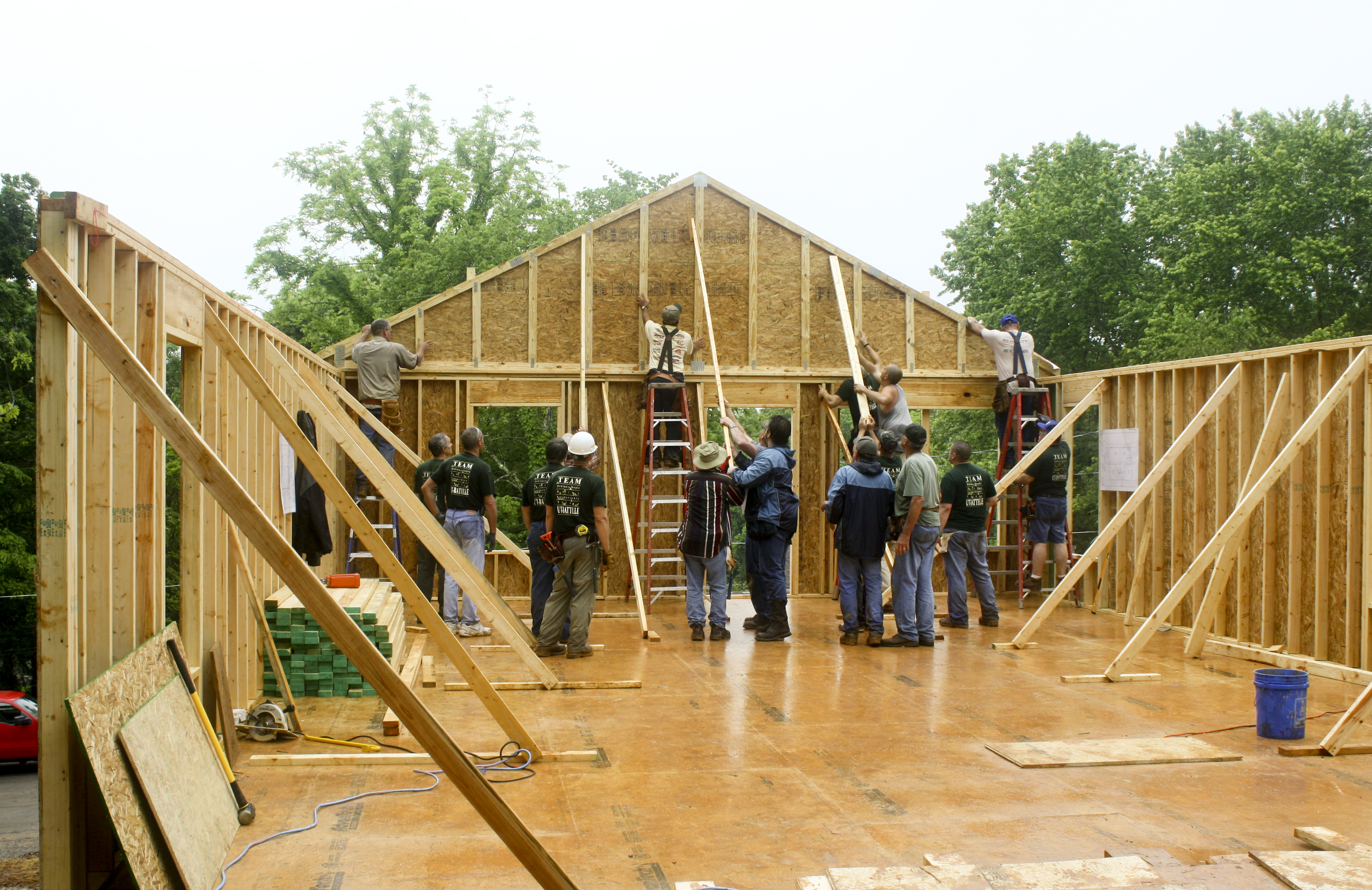 Inside of beamed walls, a team of builders places the roof beams on a house under construction.