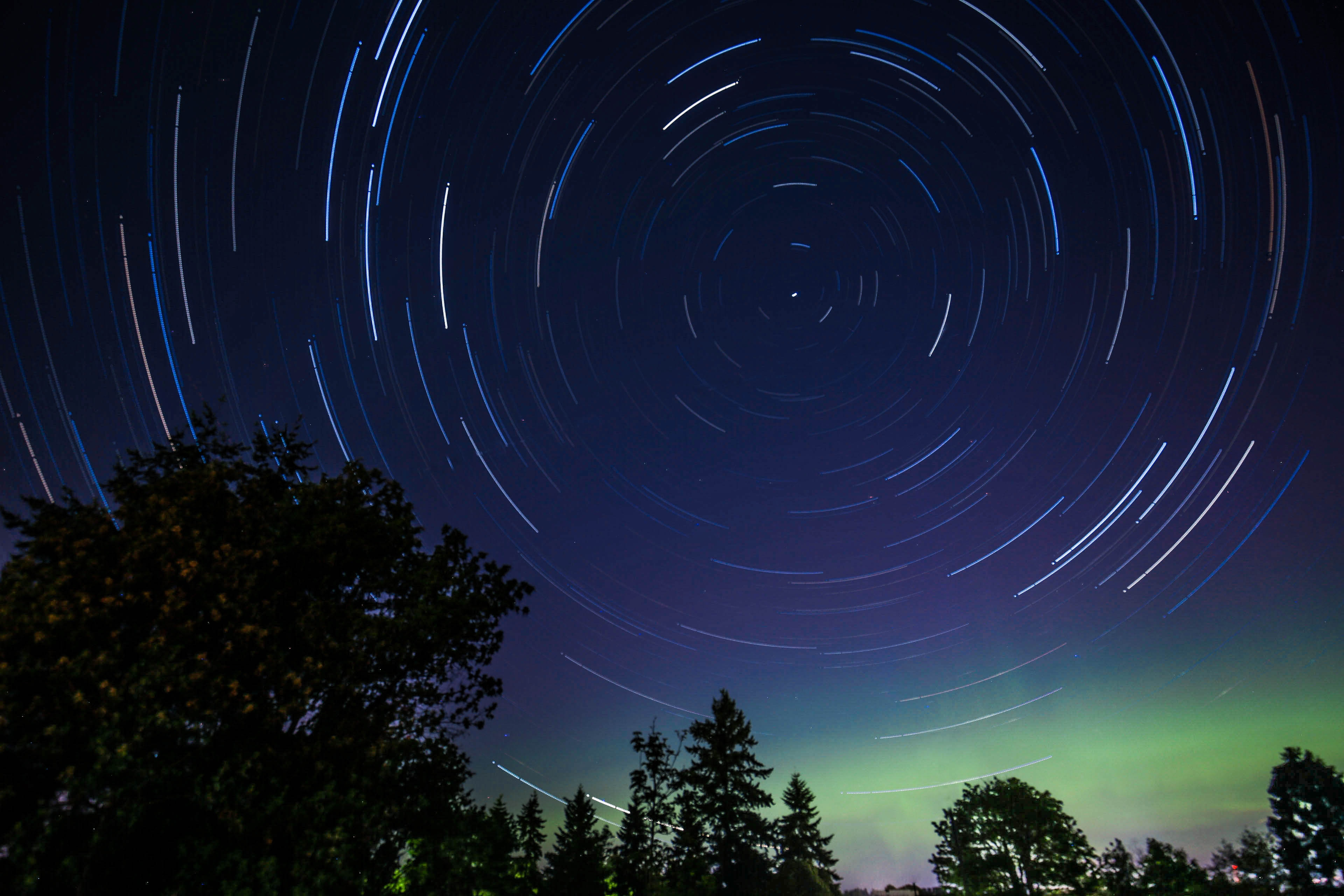 In an indigo sky, circles of stars' trails are created by leaving a camera lens open